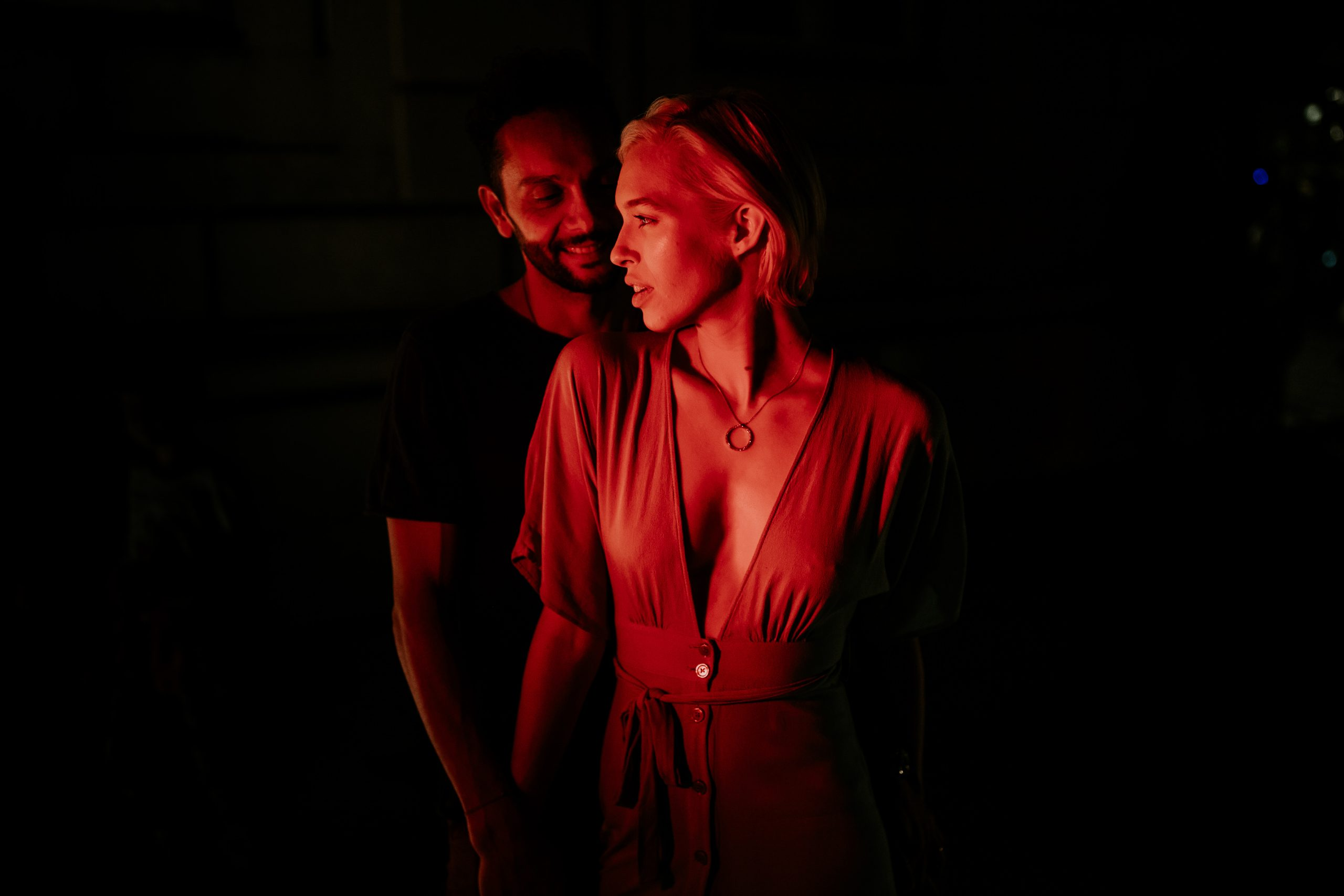 couple at night in the dark with red light on them
