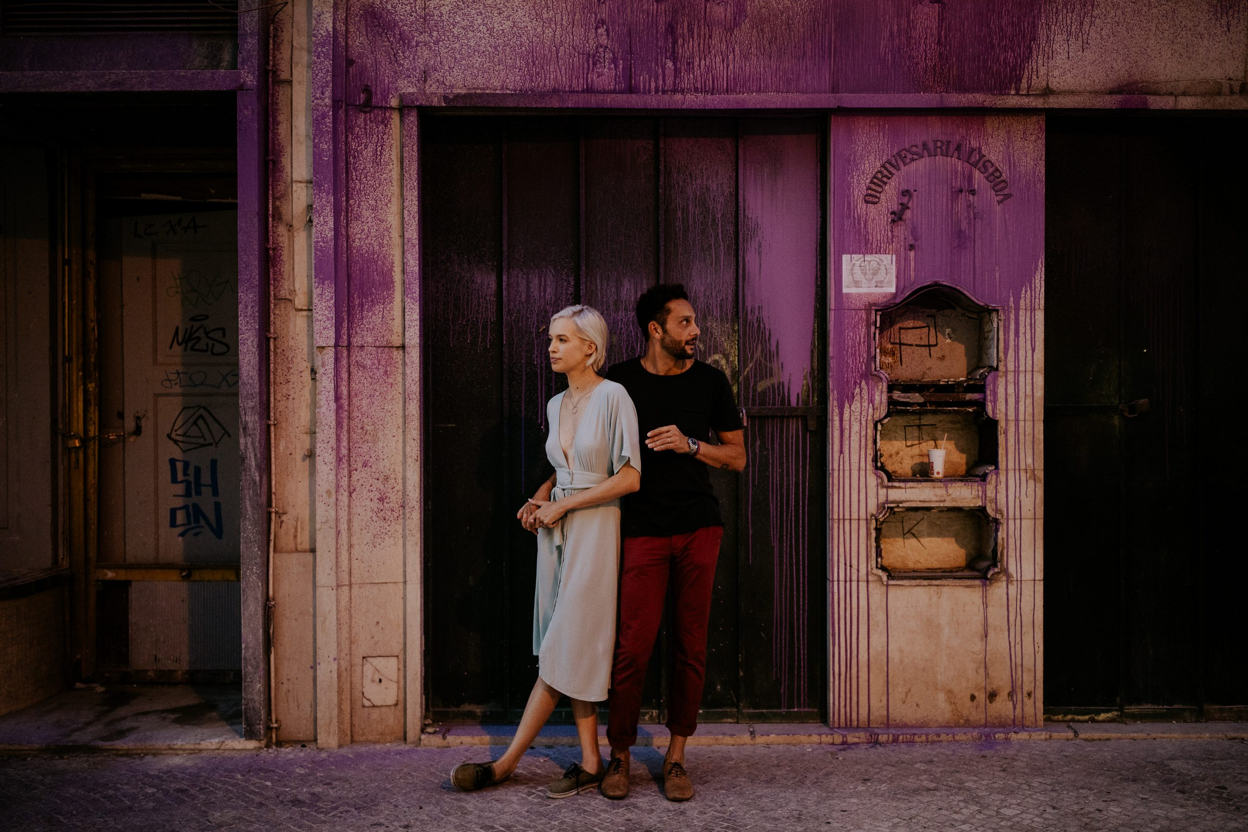 man and woman in the street next to a purple wall
