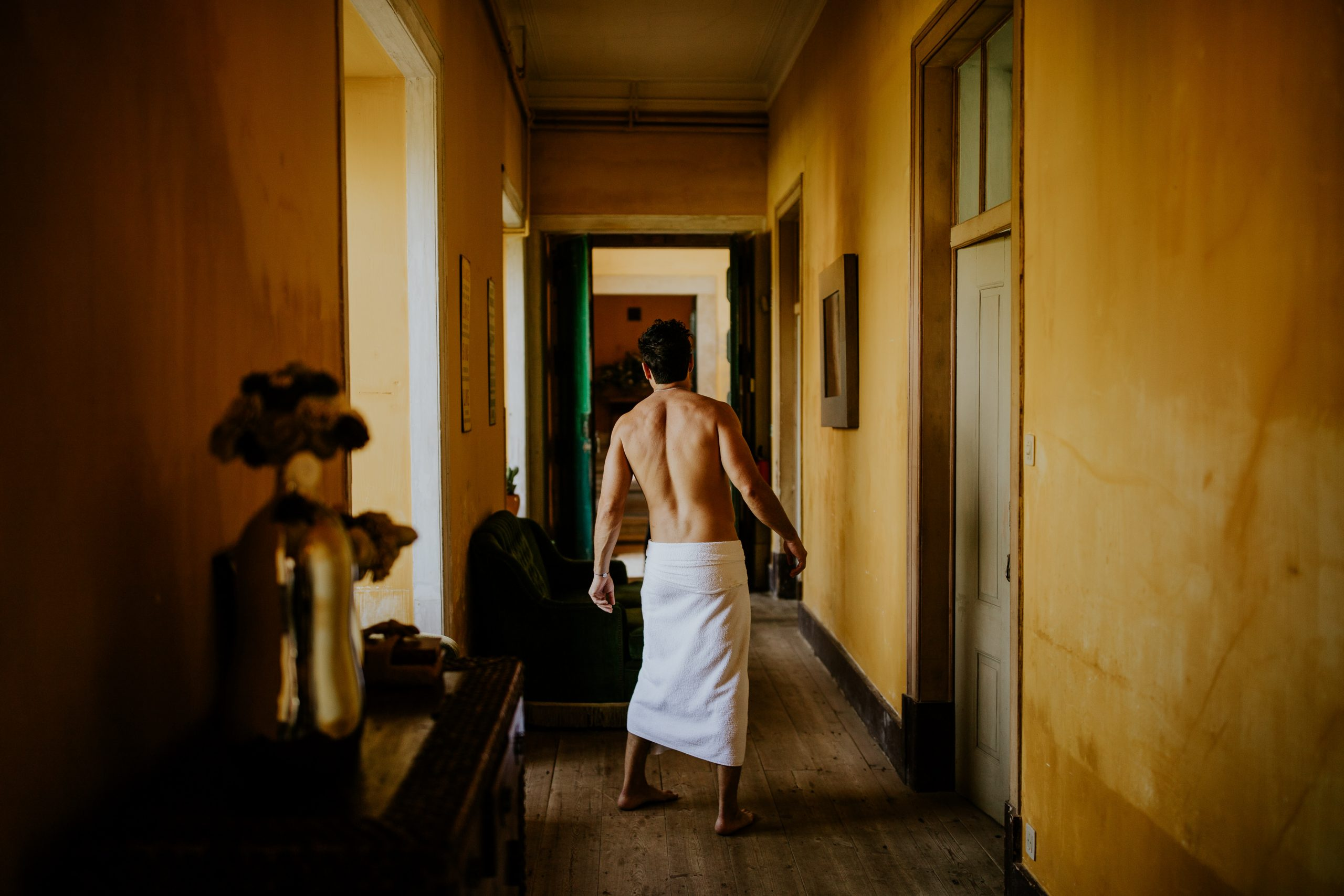 man half naked on the corridor with the bath towel