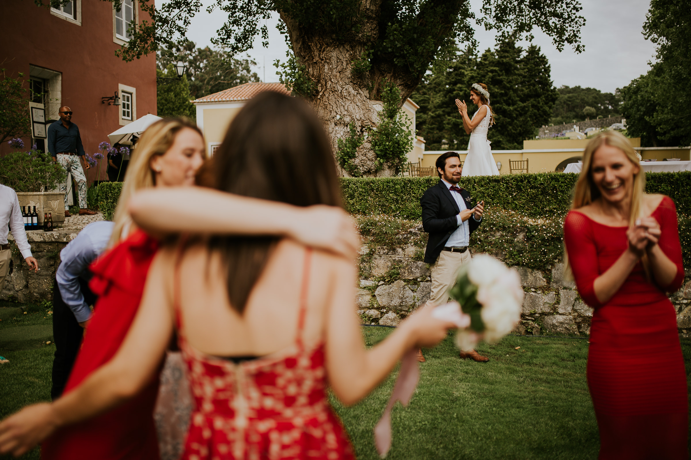 bride clapping on the background and unfocused guest with the bouquet