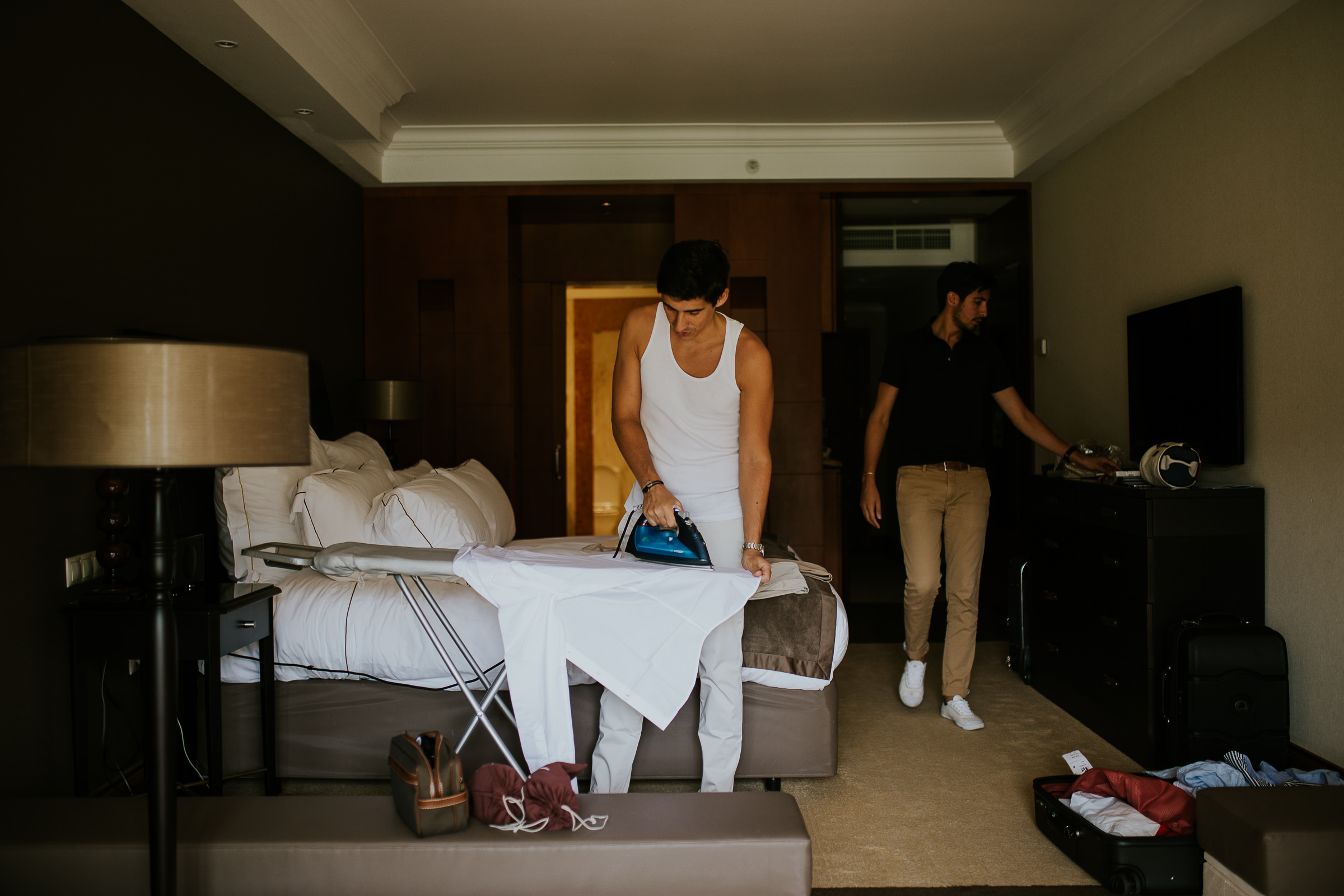 A guy ironing is white shirt in the middle of the room