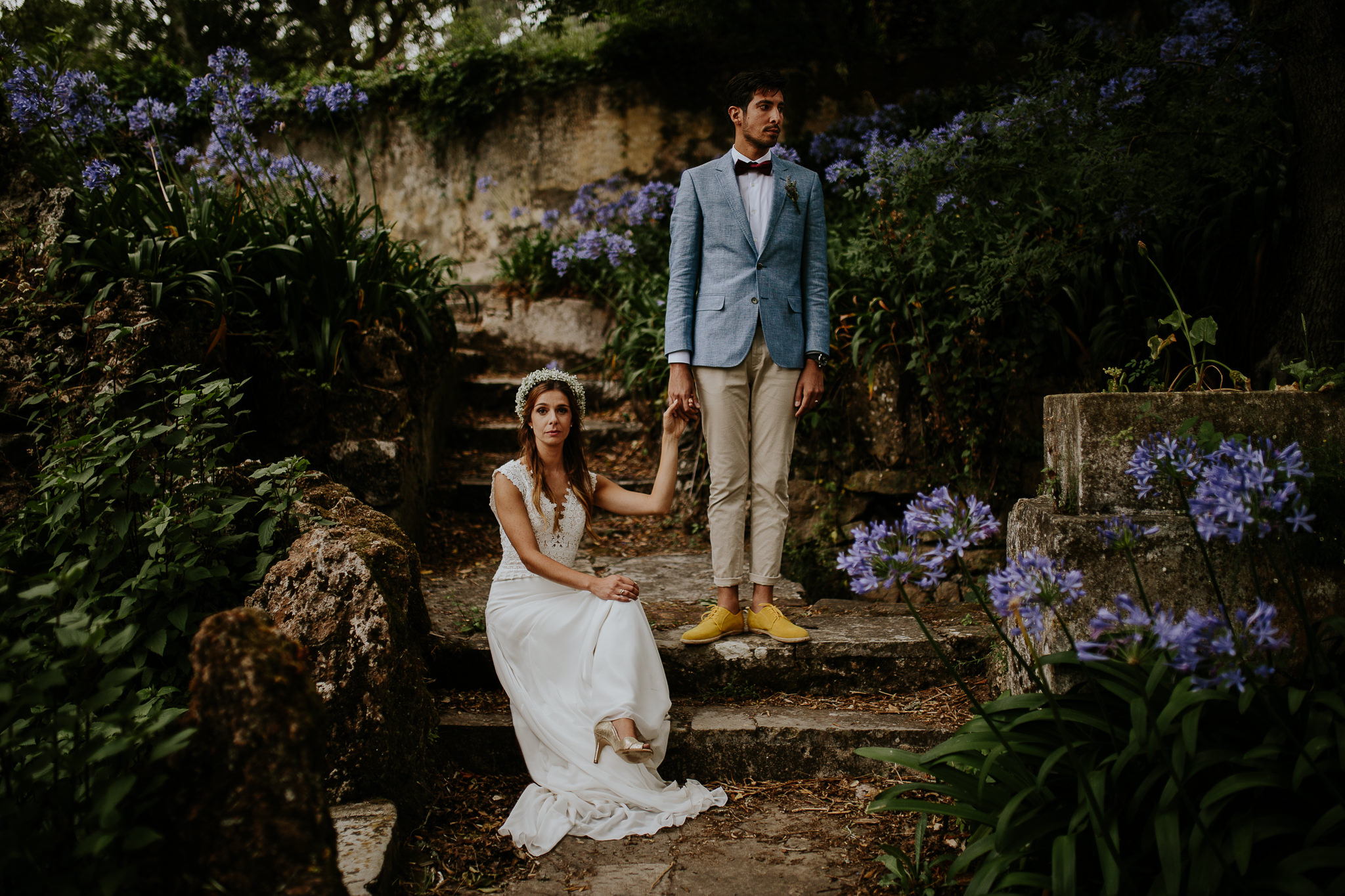 Posed portrait of sited bride and stand up groom on a garden