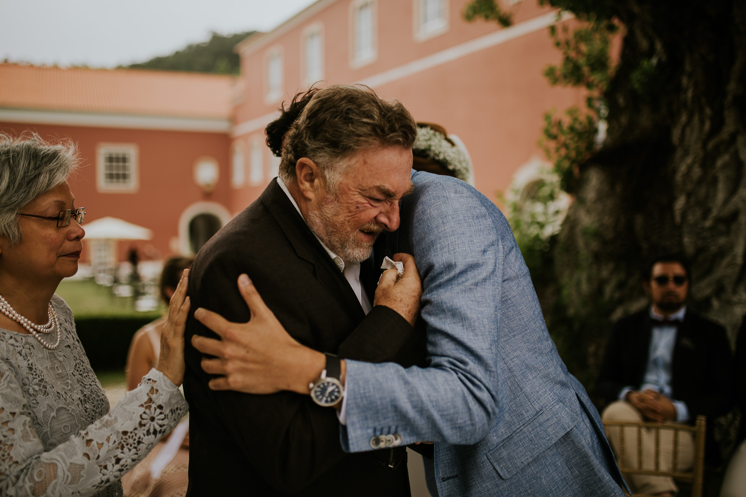 Father and groom hugging and crying