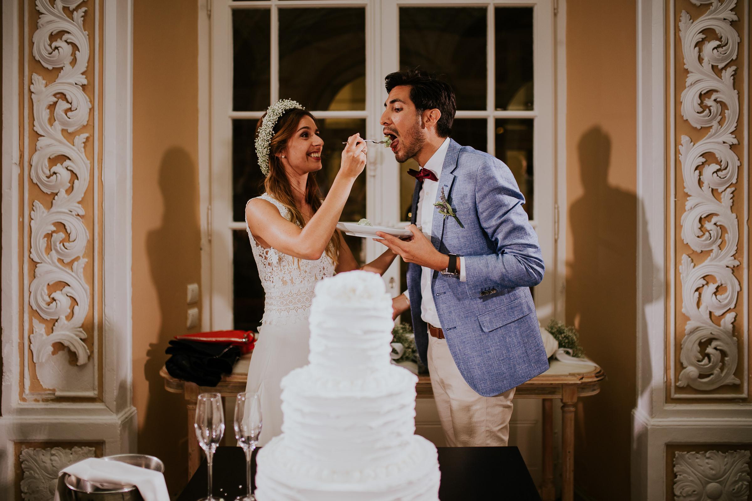 Funny bride feeding his groom with a piece od wedding cake