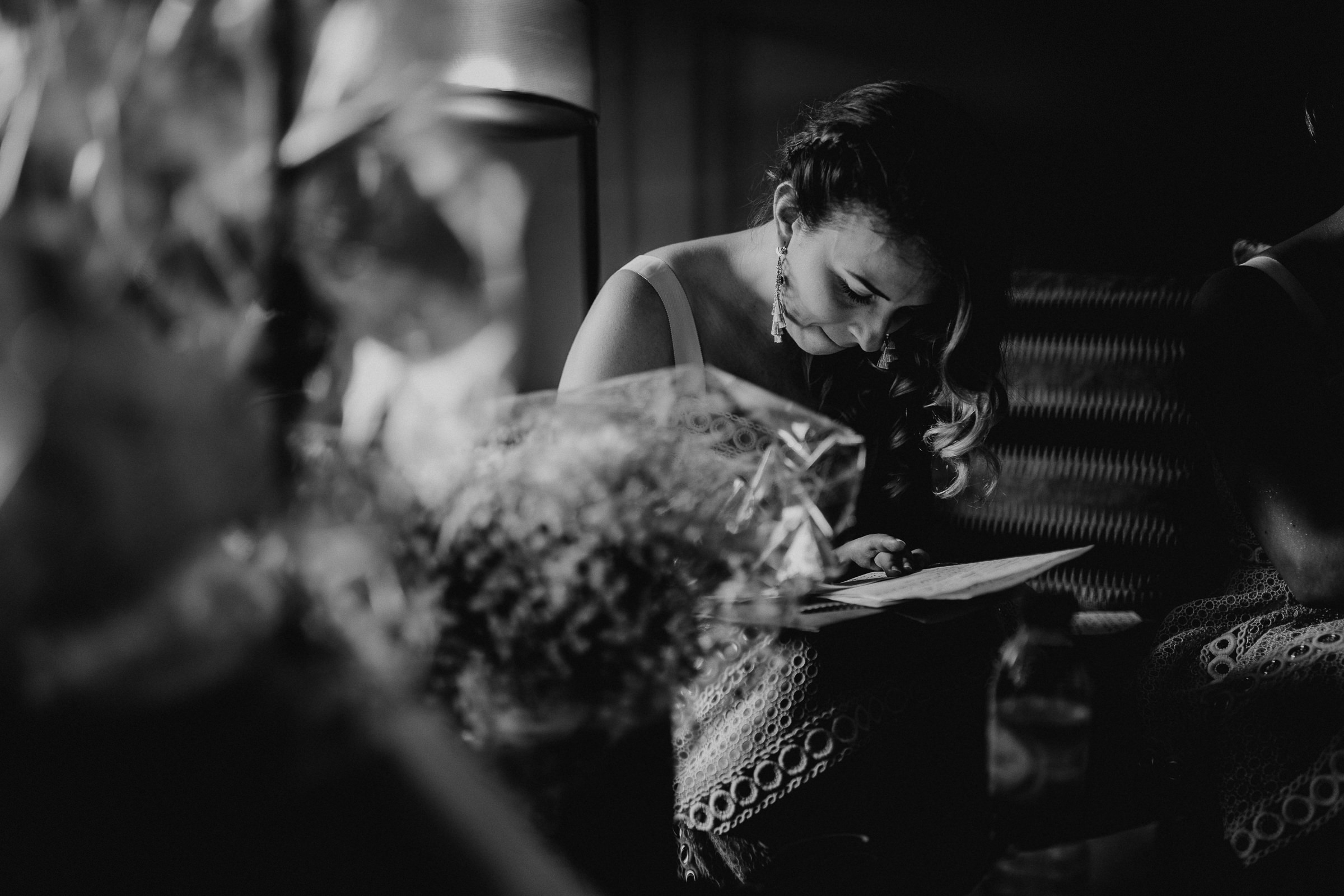 Sited bridesmaid writing her wedding vows on a piece of paper