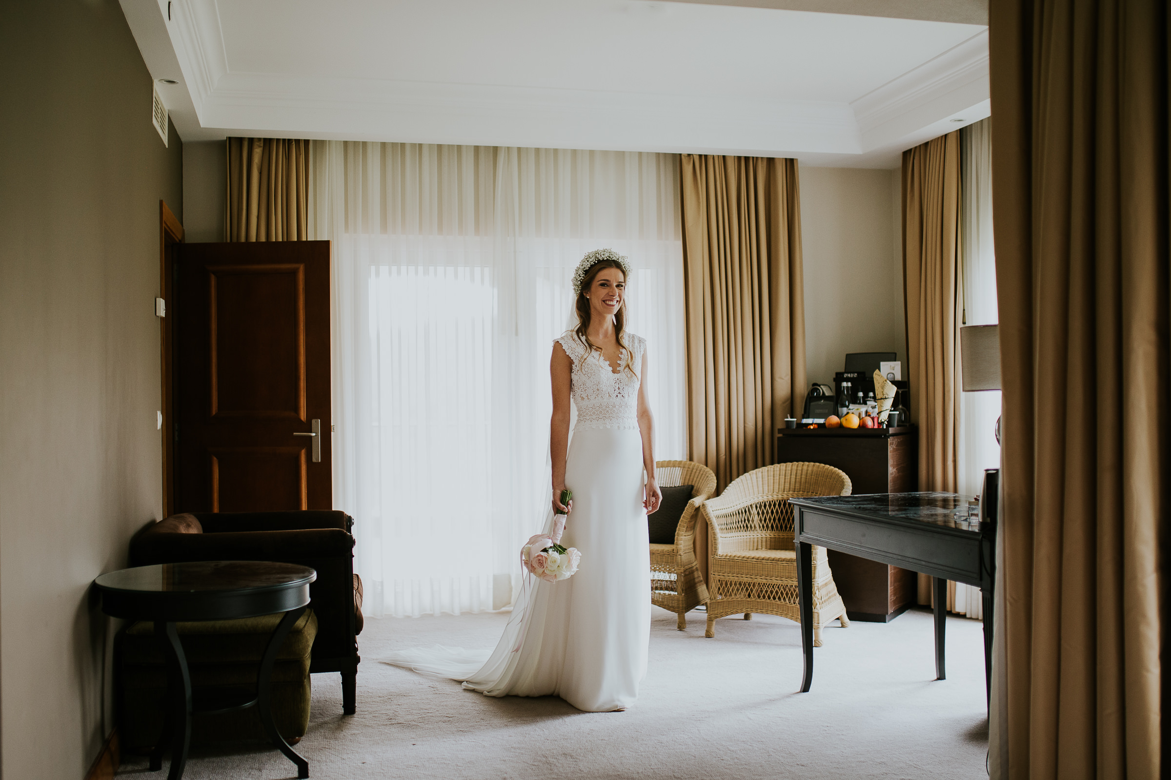 Centered portrait of the bride holing her bouquet in the middle of an hotel room