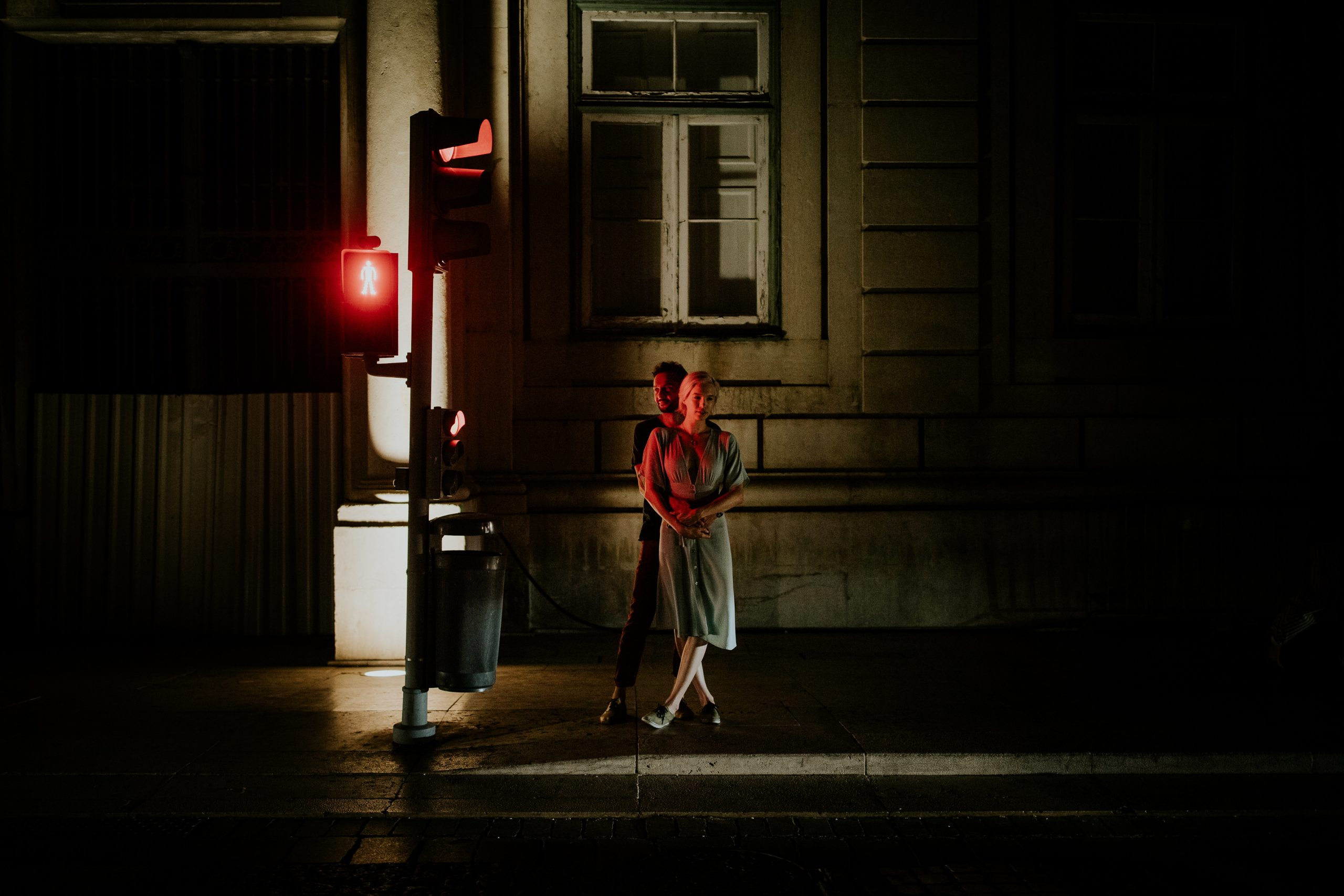 couple embrace at night next to a red traffic light
