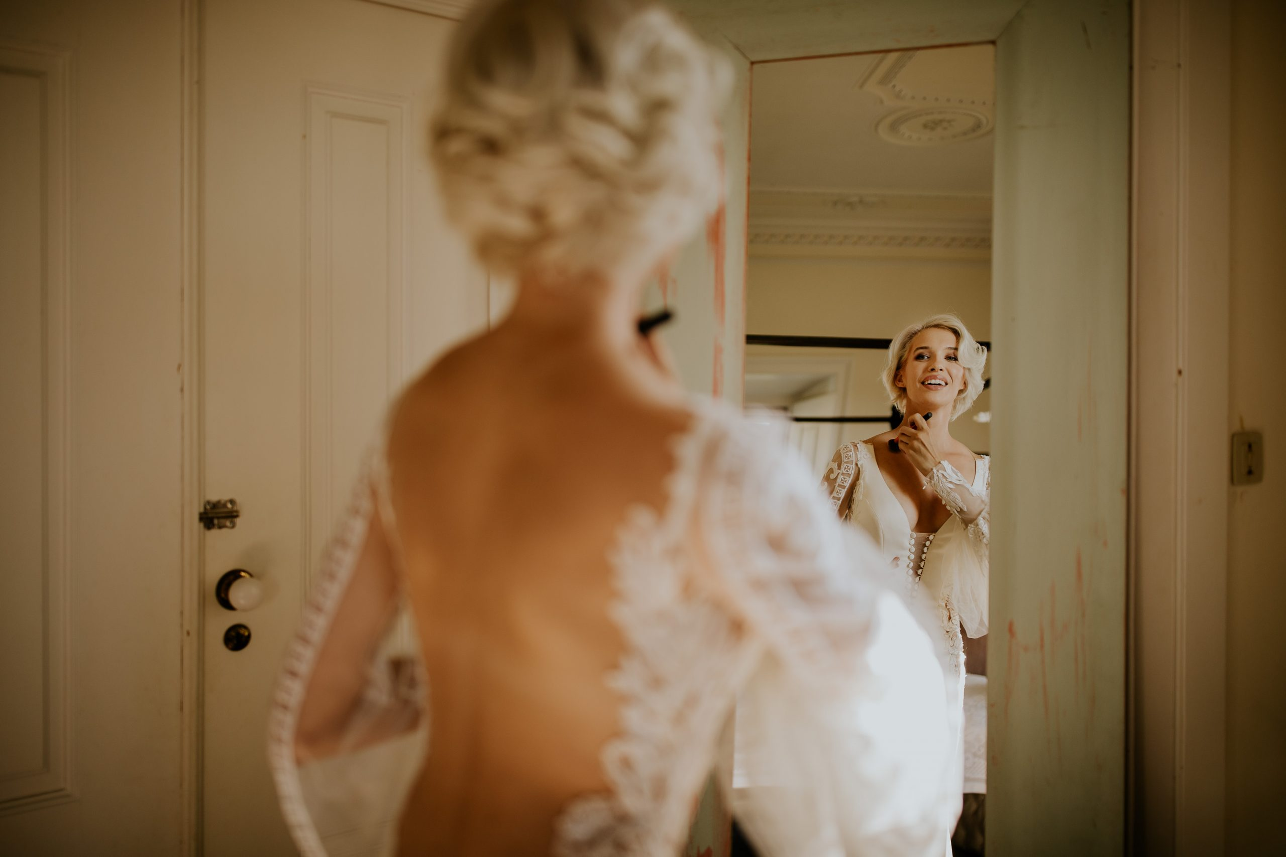 bride getting ready and looking at the mirror