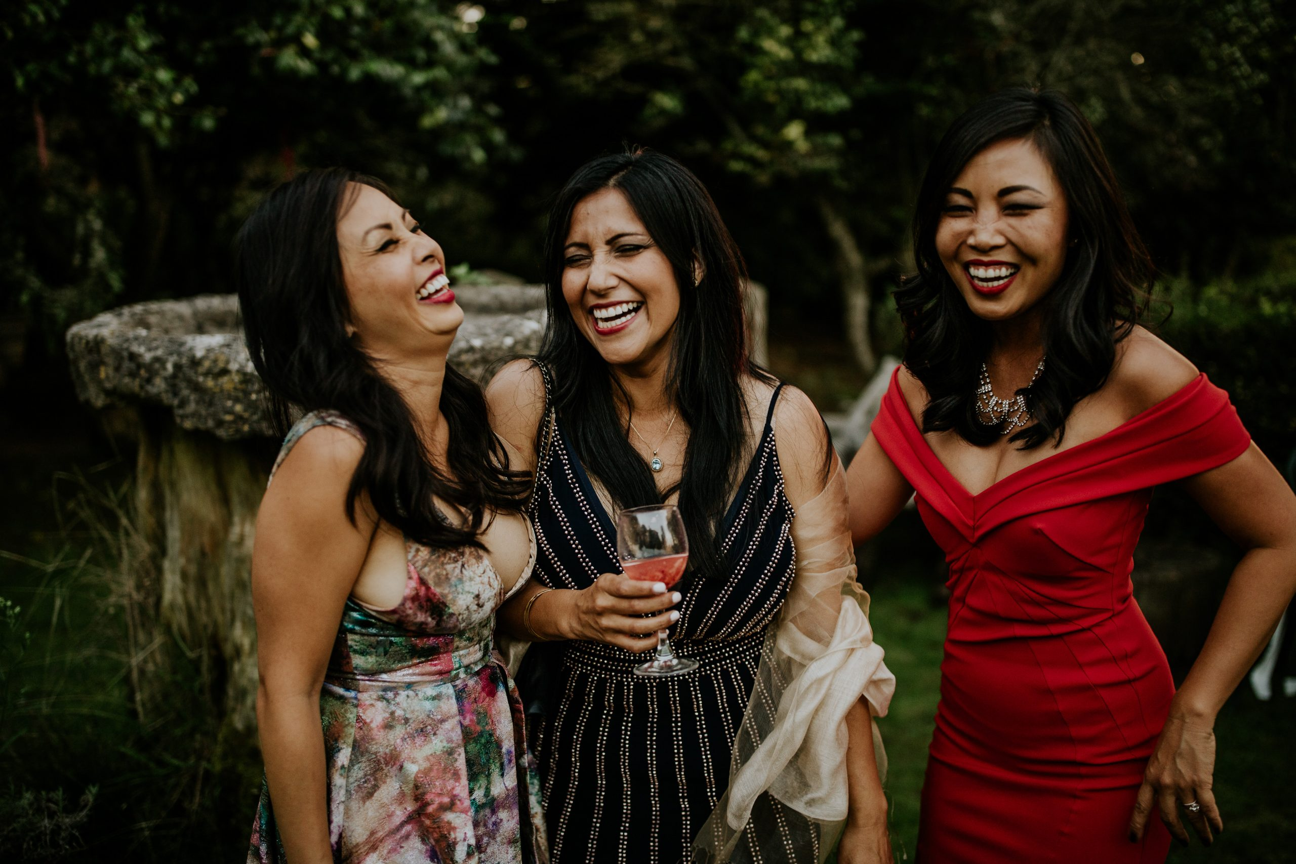 three woman smiling to the camera on a wedding cocktail