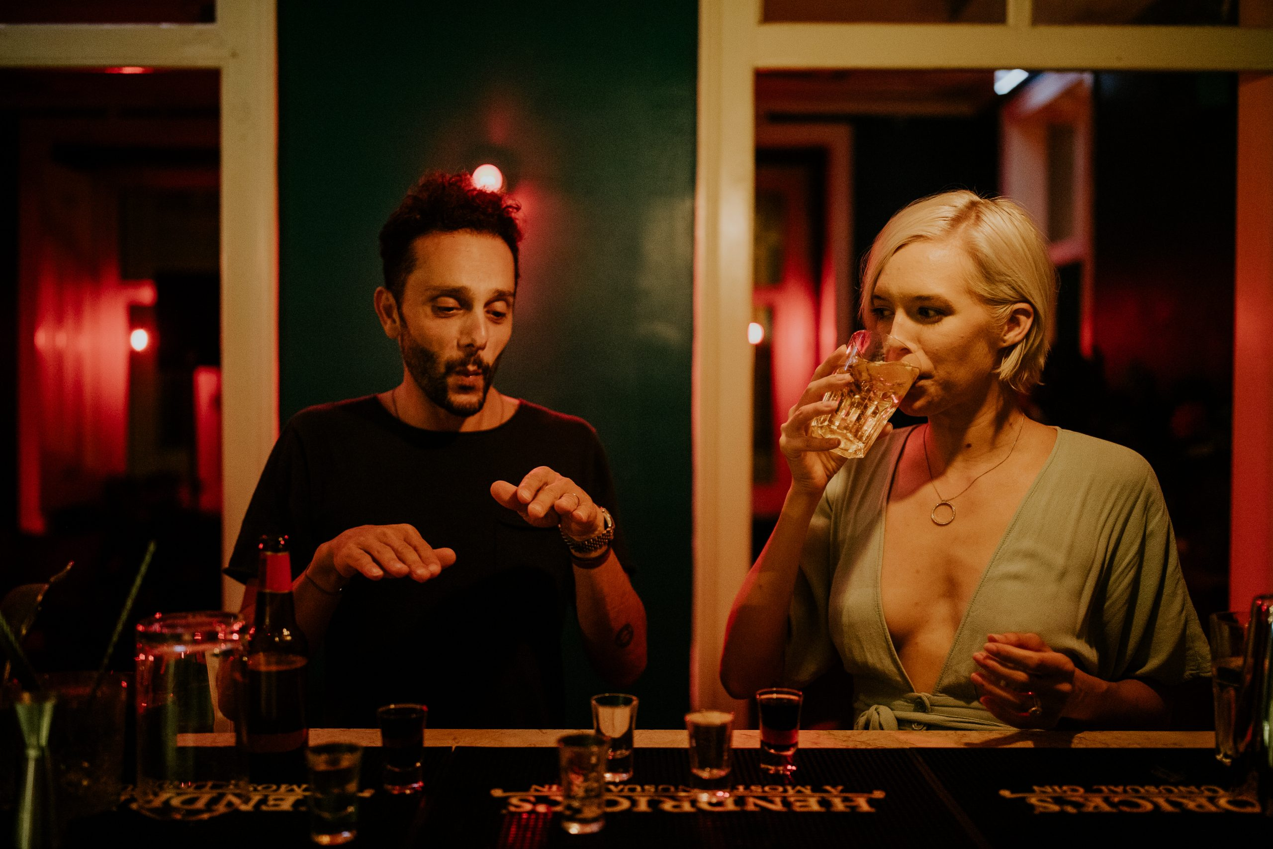 man and woman having drinks and shots on a bar at night