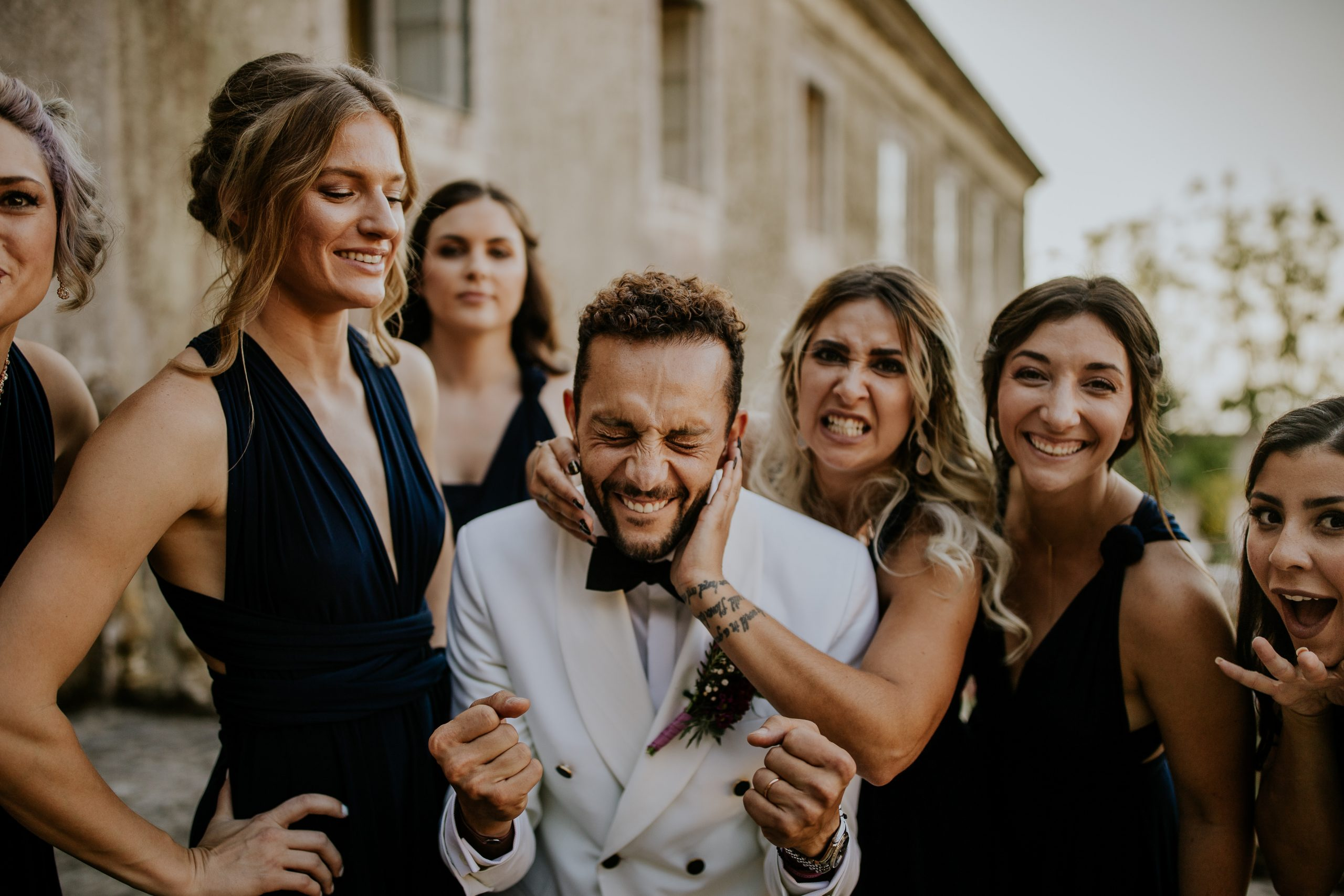 happy groom rounded by girls