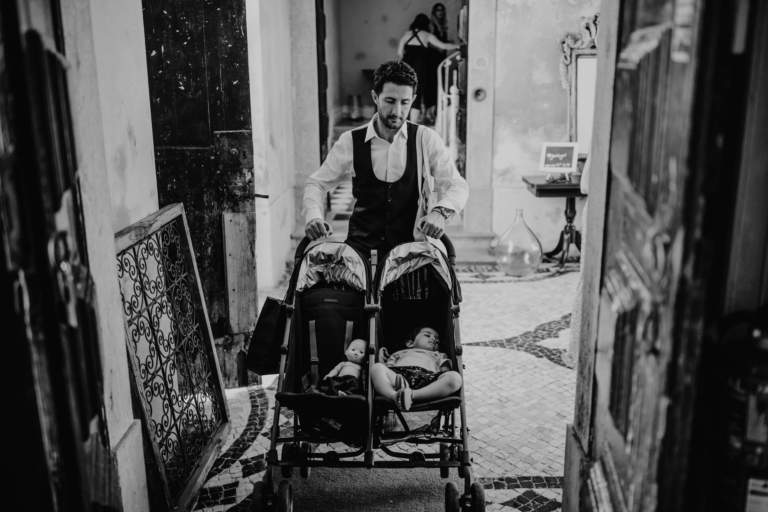 man carrying a twin baby car with a baby and a doll