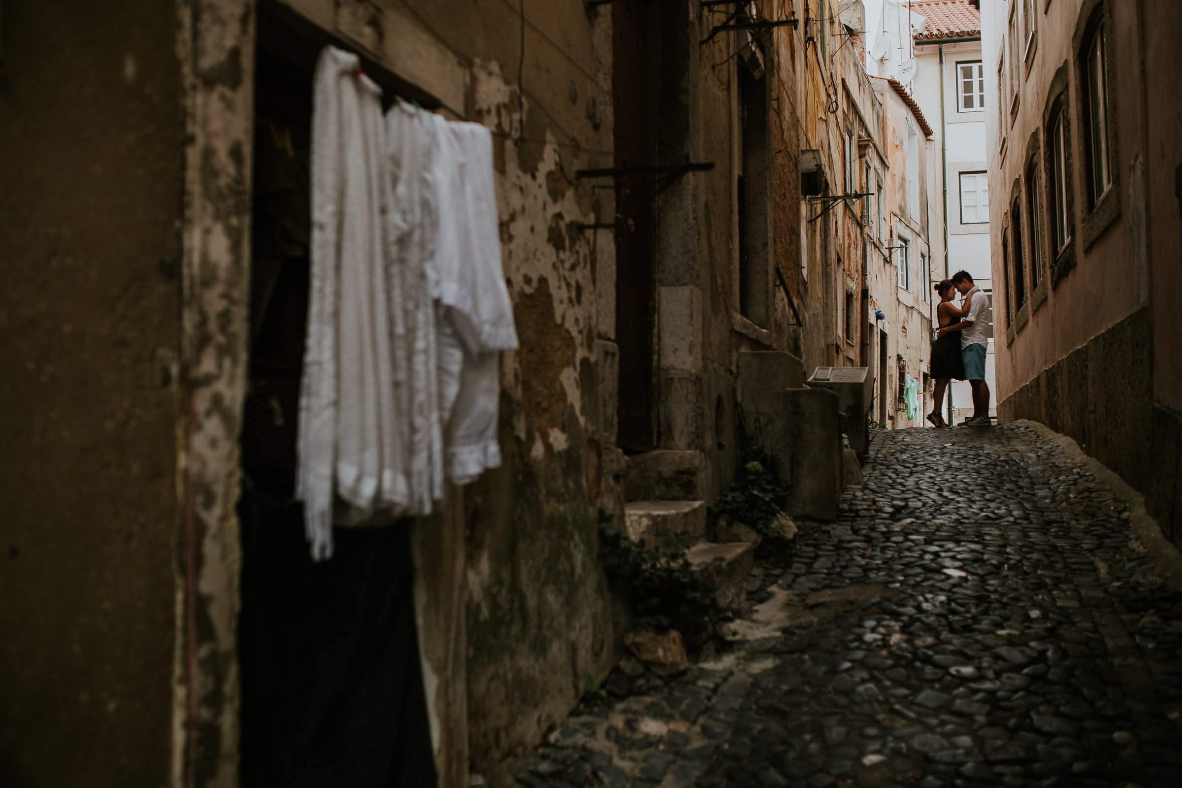 couple embraced in lisbon streets with clothesline