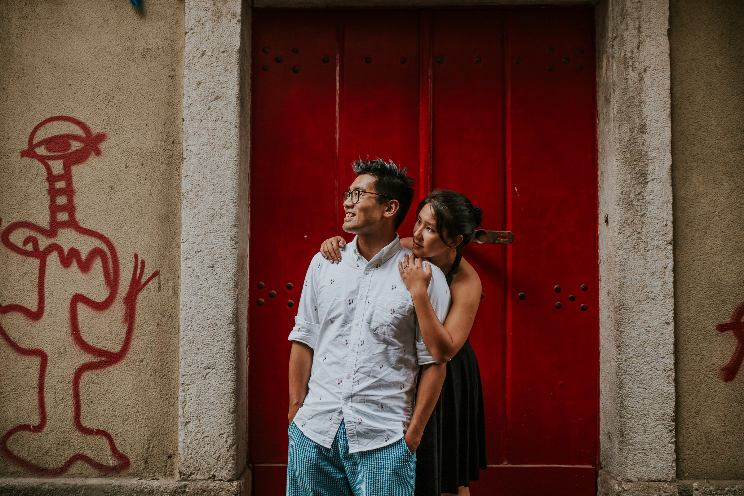 asian couple embraced with a red door as background in lisbon
