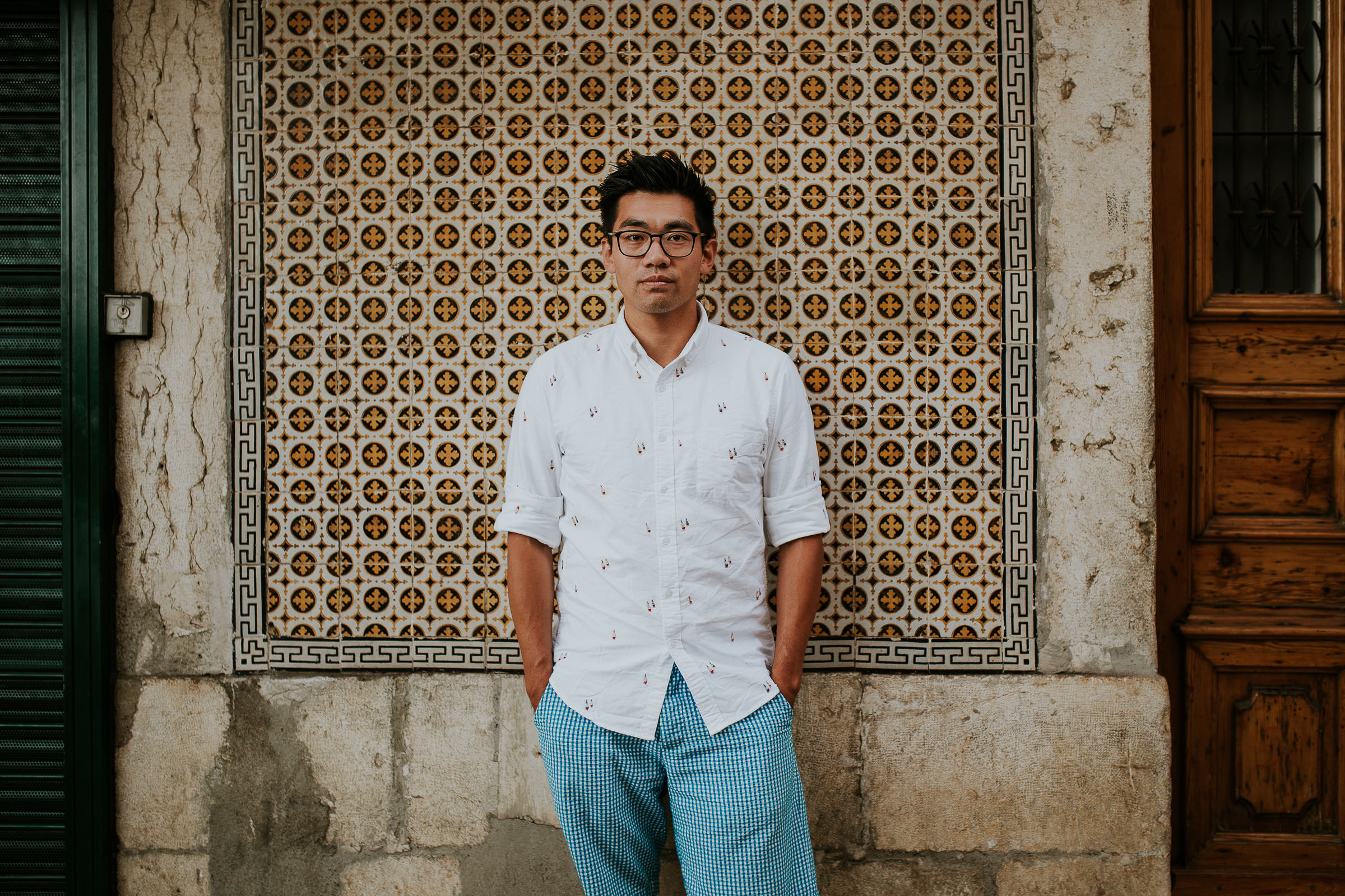 asian man in lisbon street with tiles in background