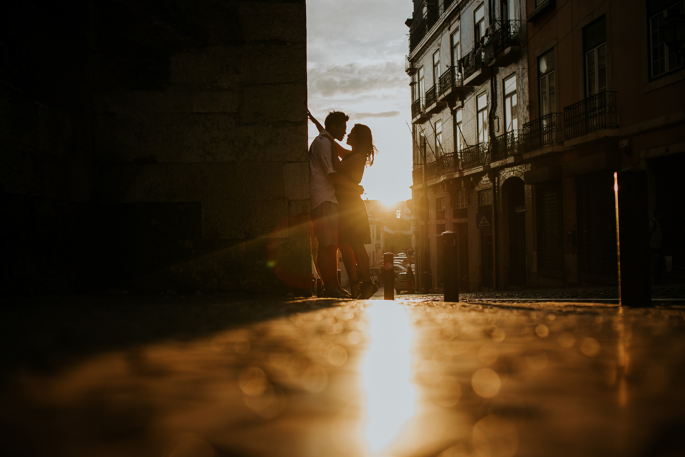 asian couple embraced during the sunset in lisbon streets