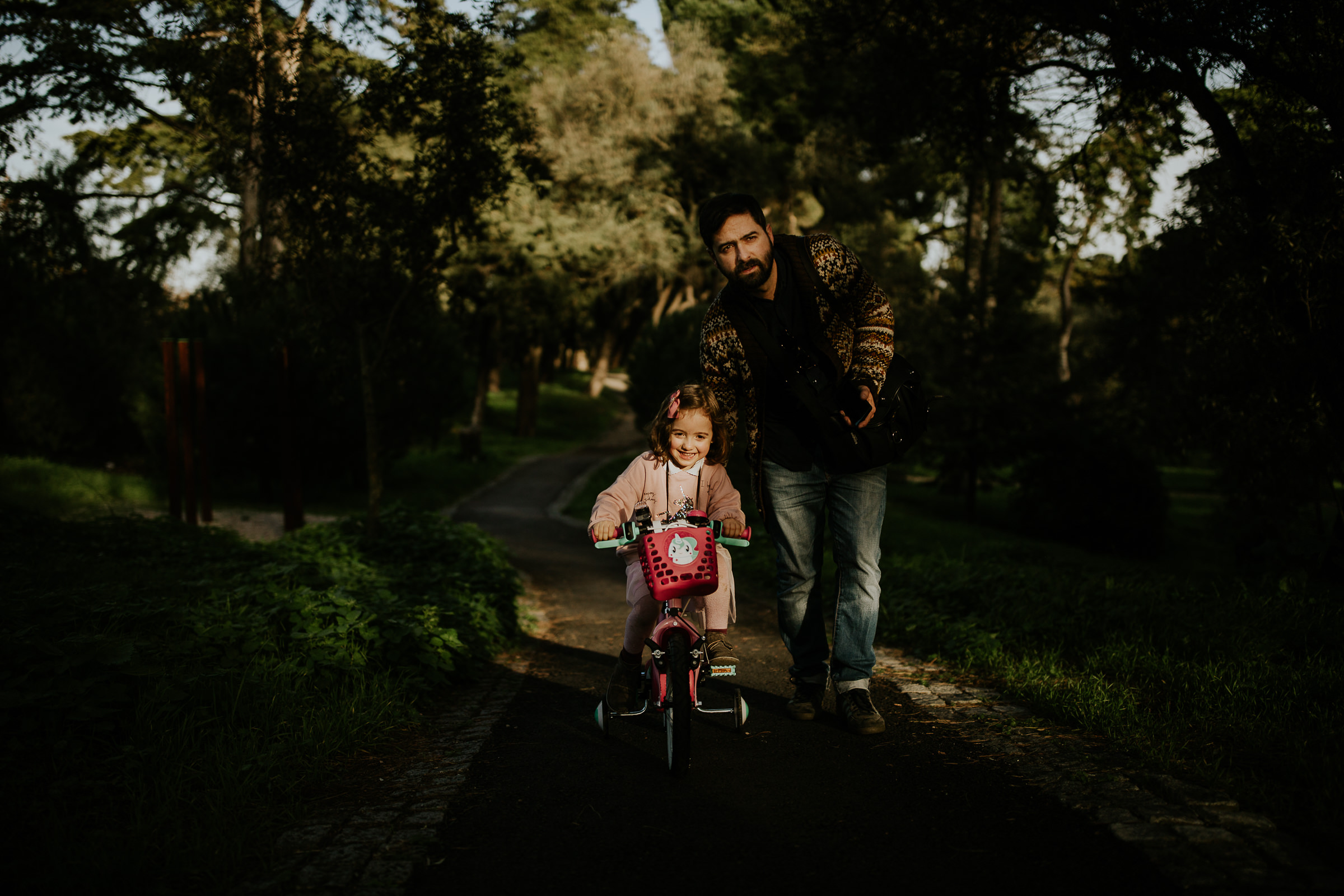 daughter riding a bike helped by her father