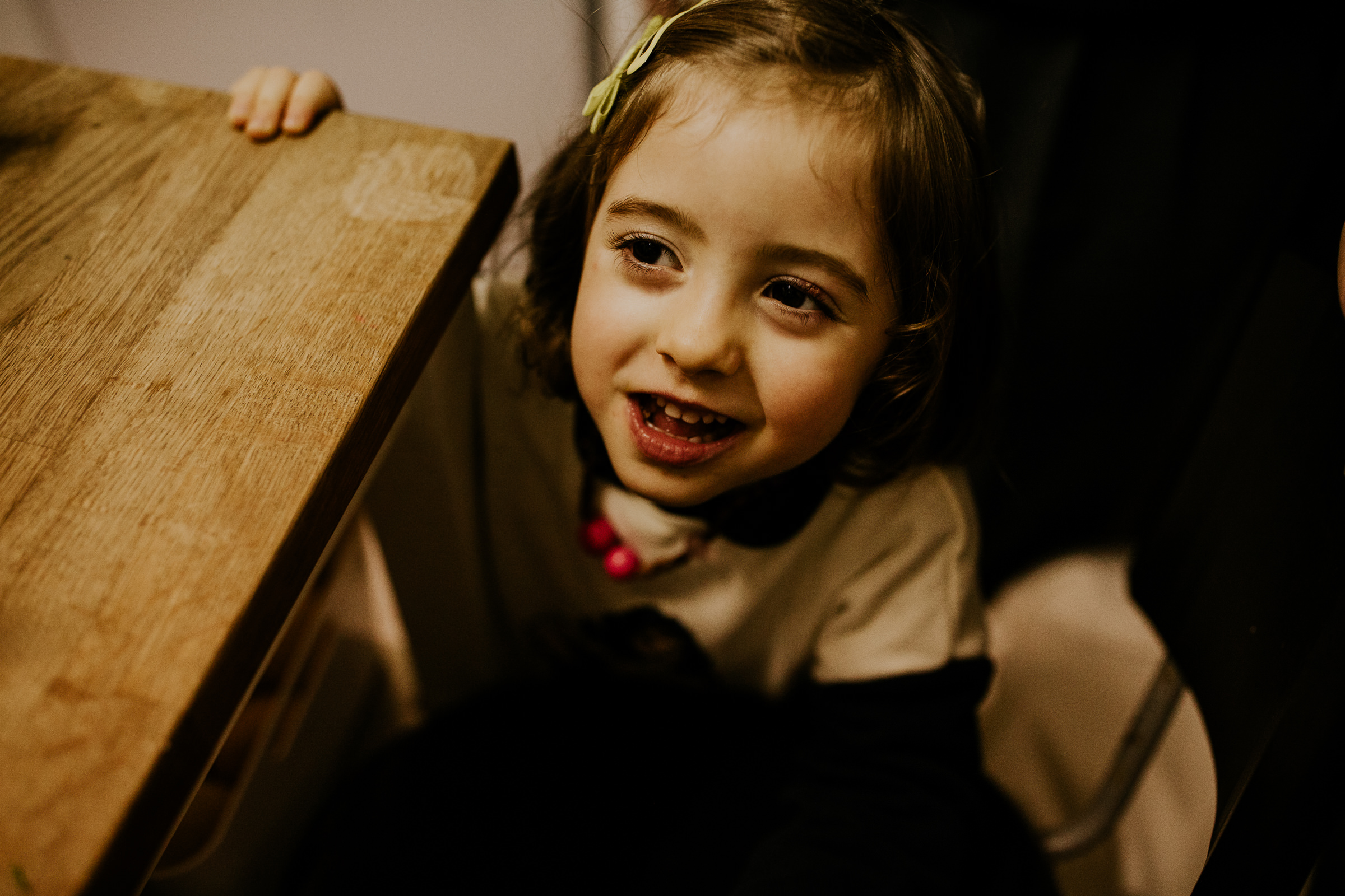 little child smiling next to a table at home