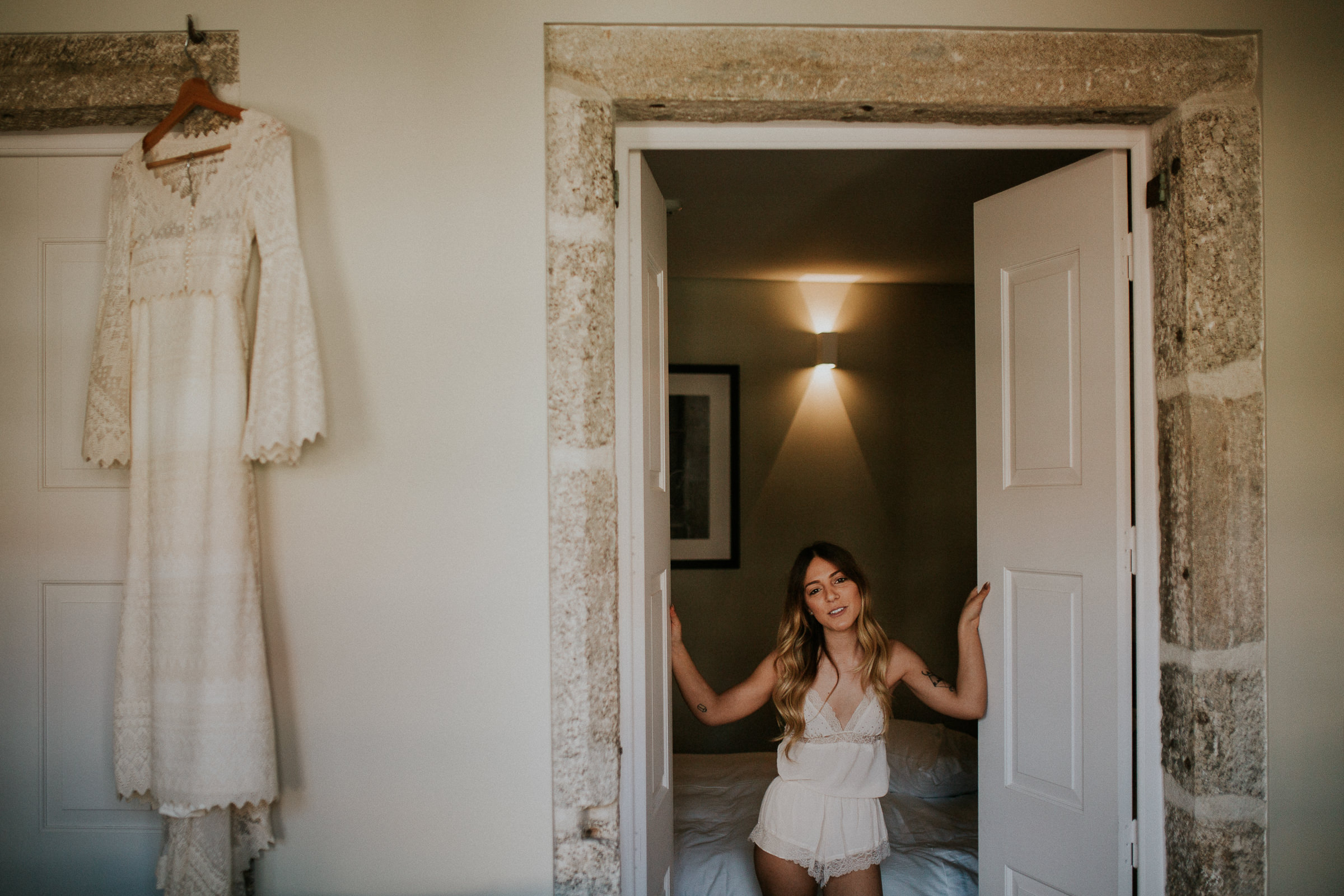 bride getting ready with her boho chic wedding dress hanged