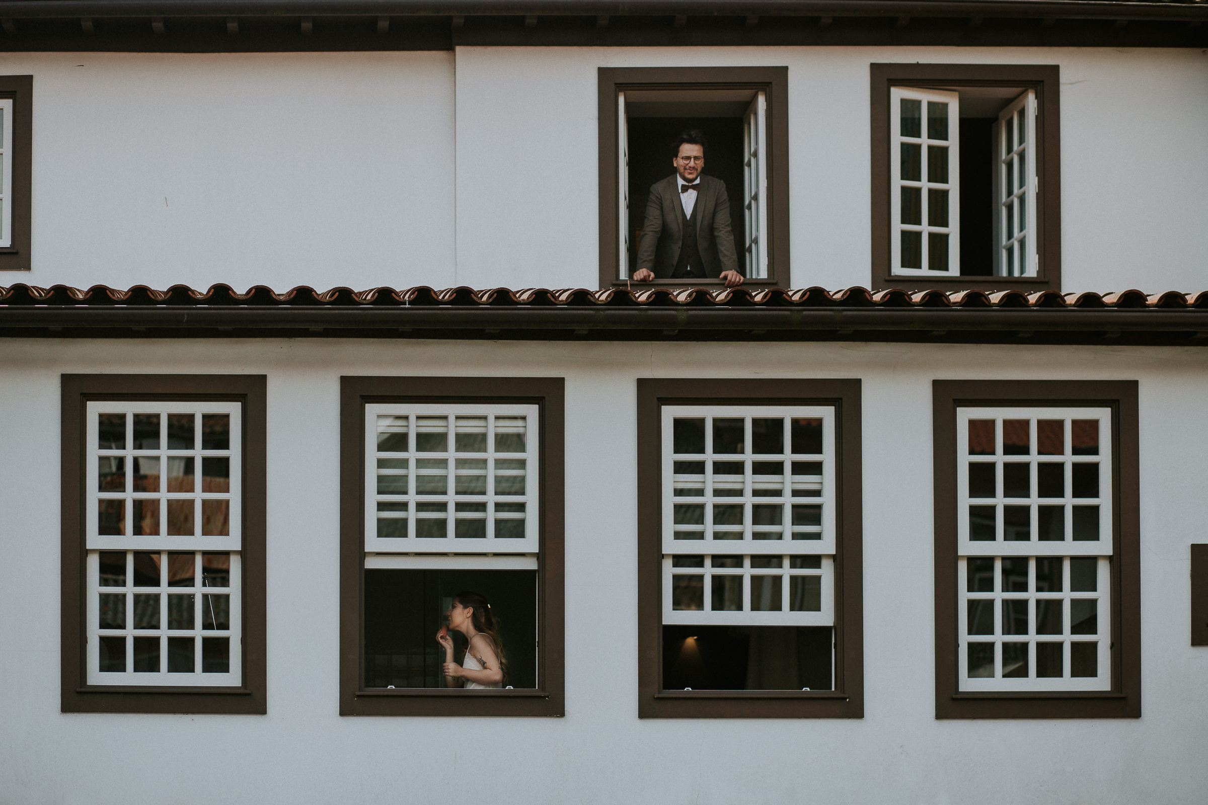 bride and groom getting ready on different floors from a building outside view