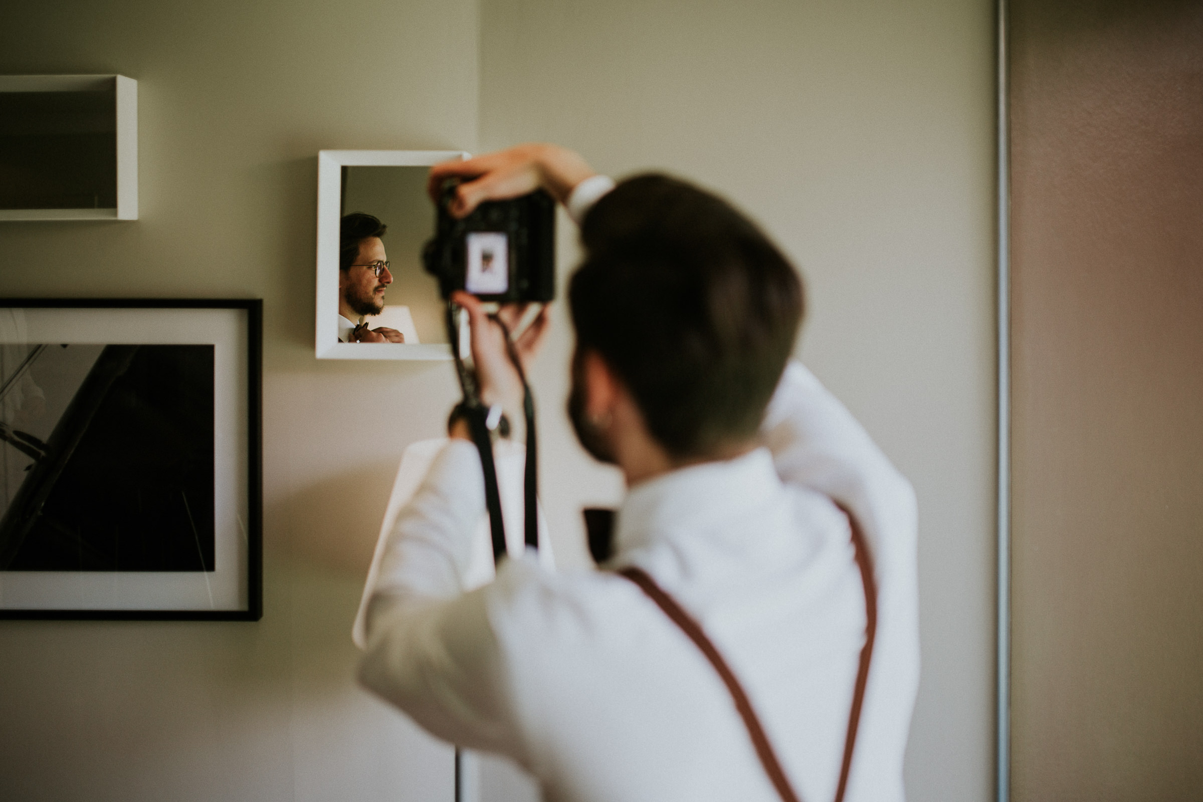 wedding guest taking a photo of a groom on the mirror reflection