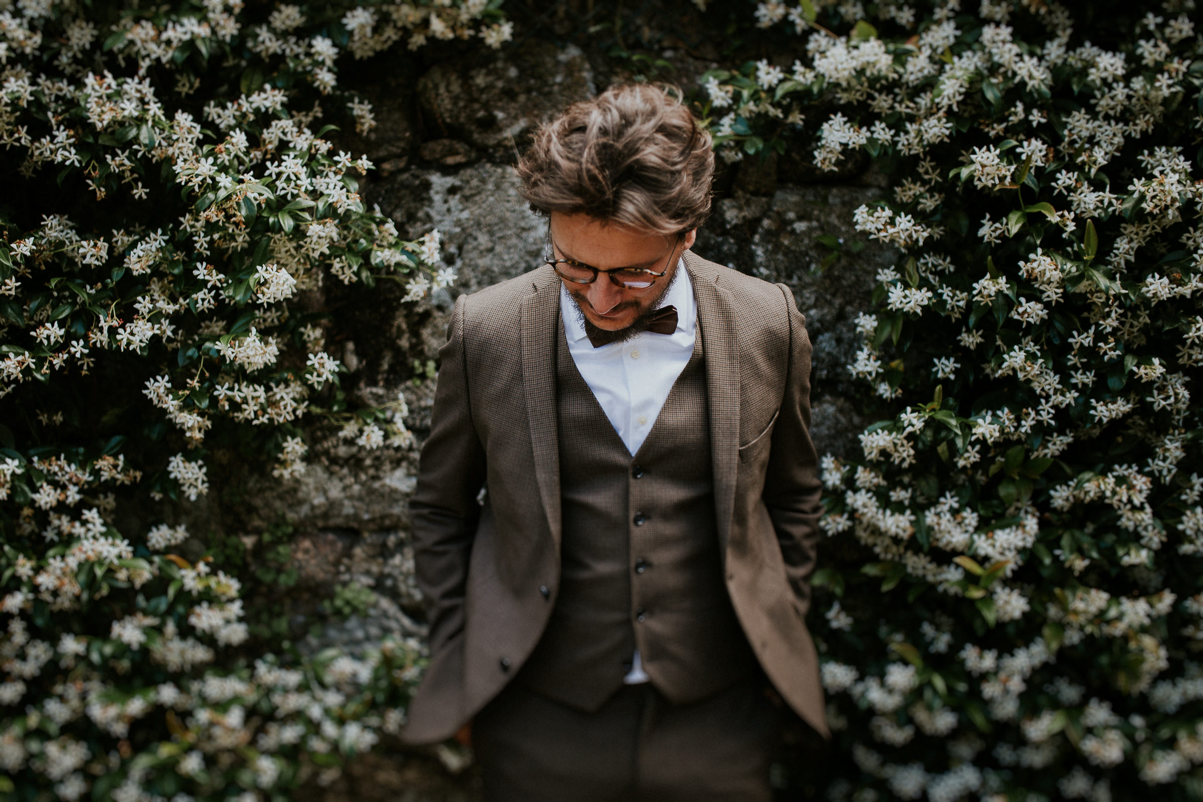 boho chic groom portrait with flowers on the wall