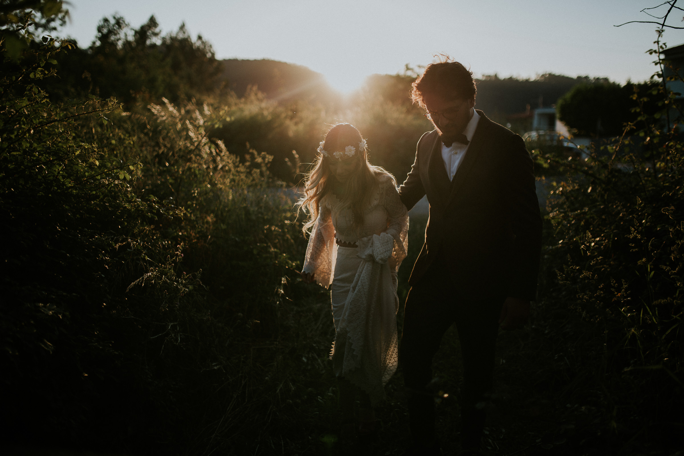 bride and groom walking in the woods during the sunset