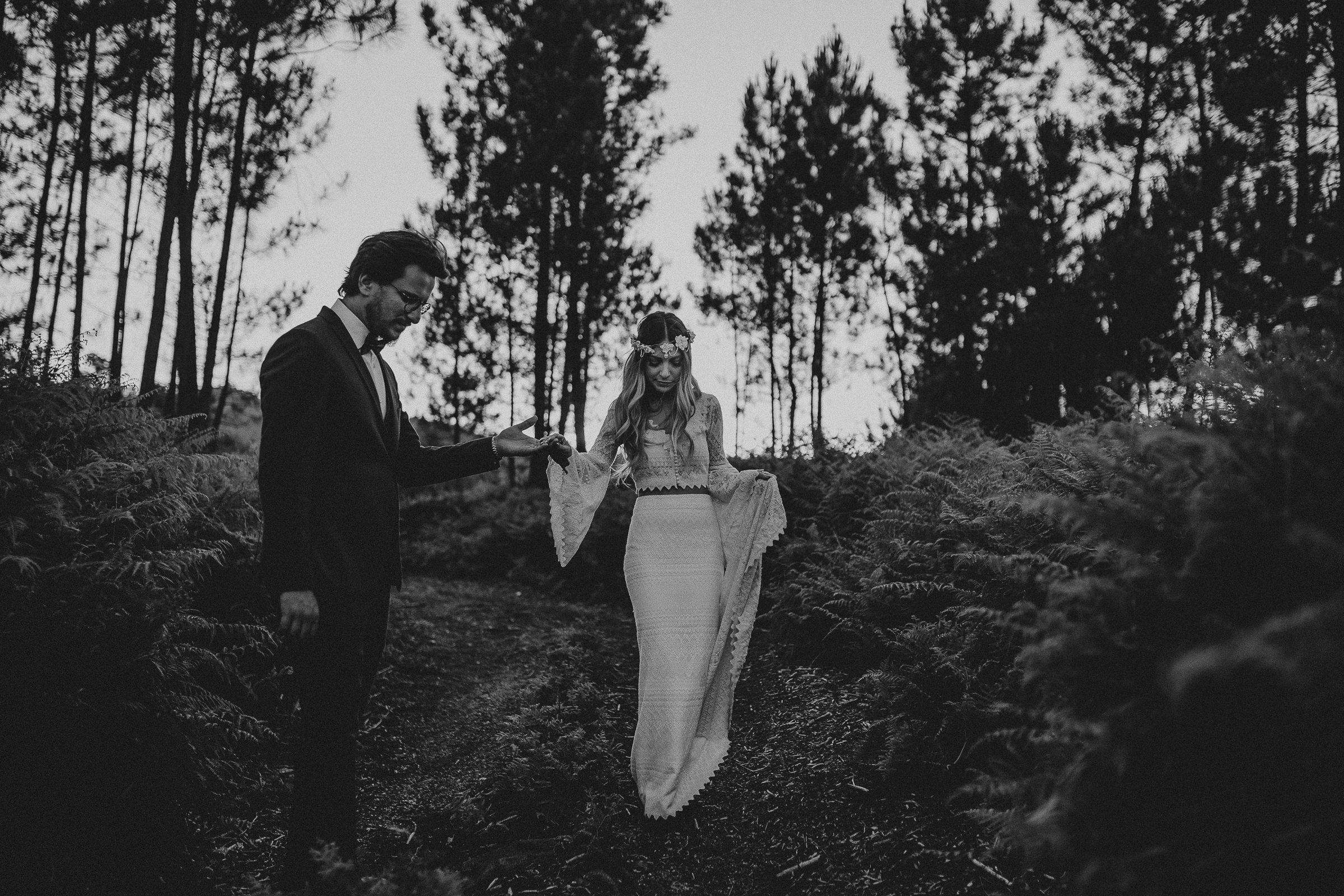 black and white photo of bride and groom in the woods holding hands