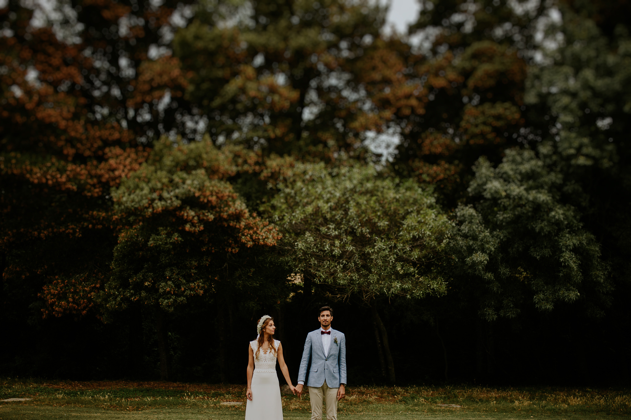 Strait portrait of bride and groom surrounded by Trees