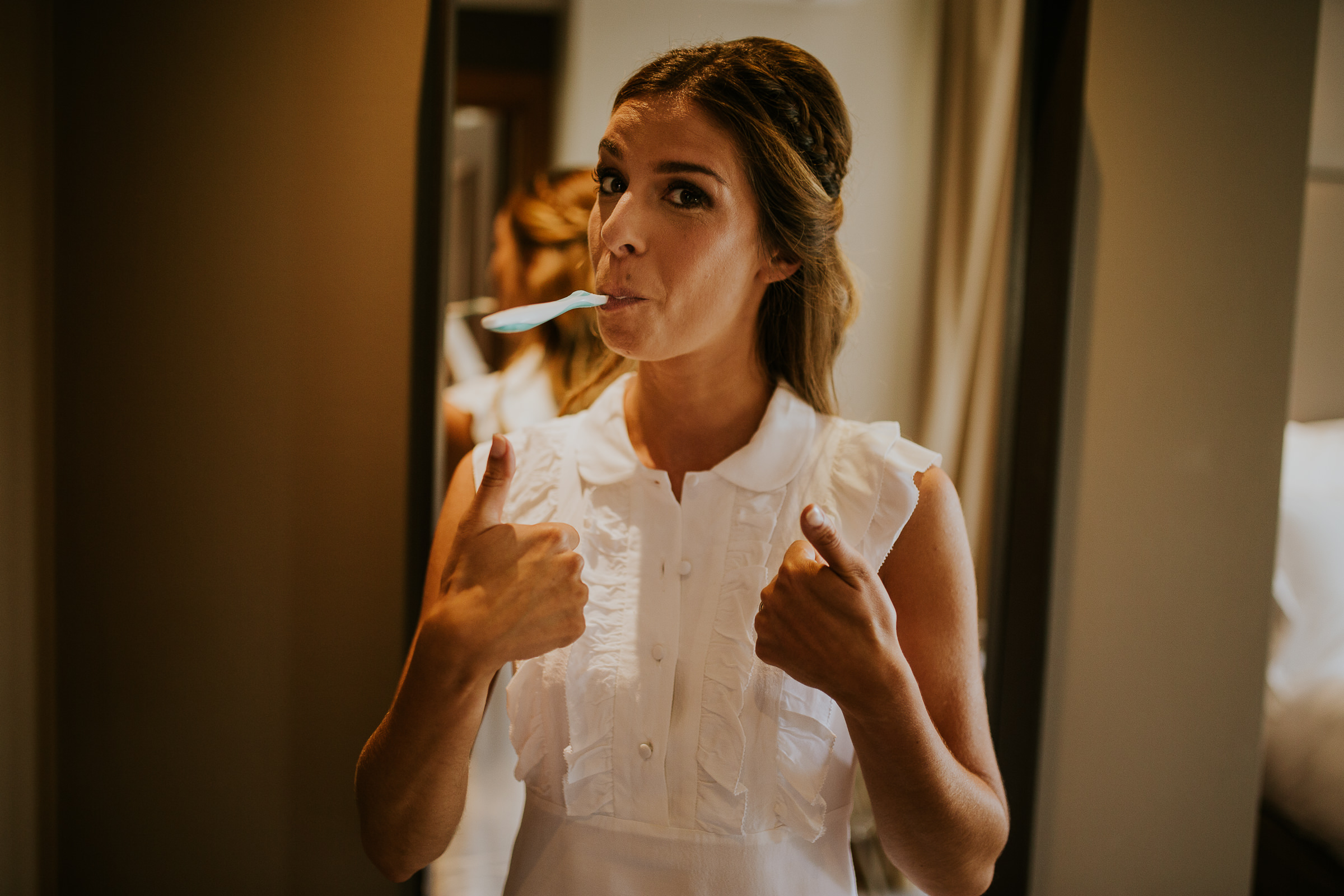 Woman brushing her teeth and doing thumbs up