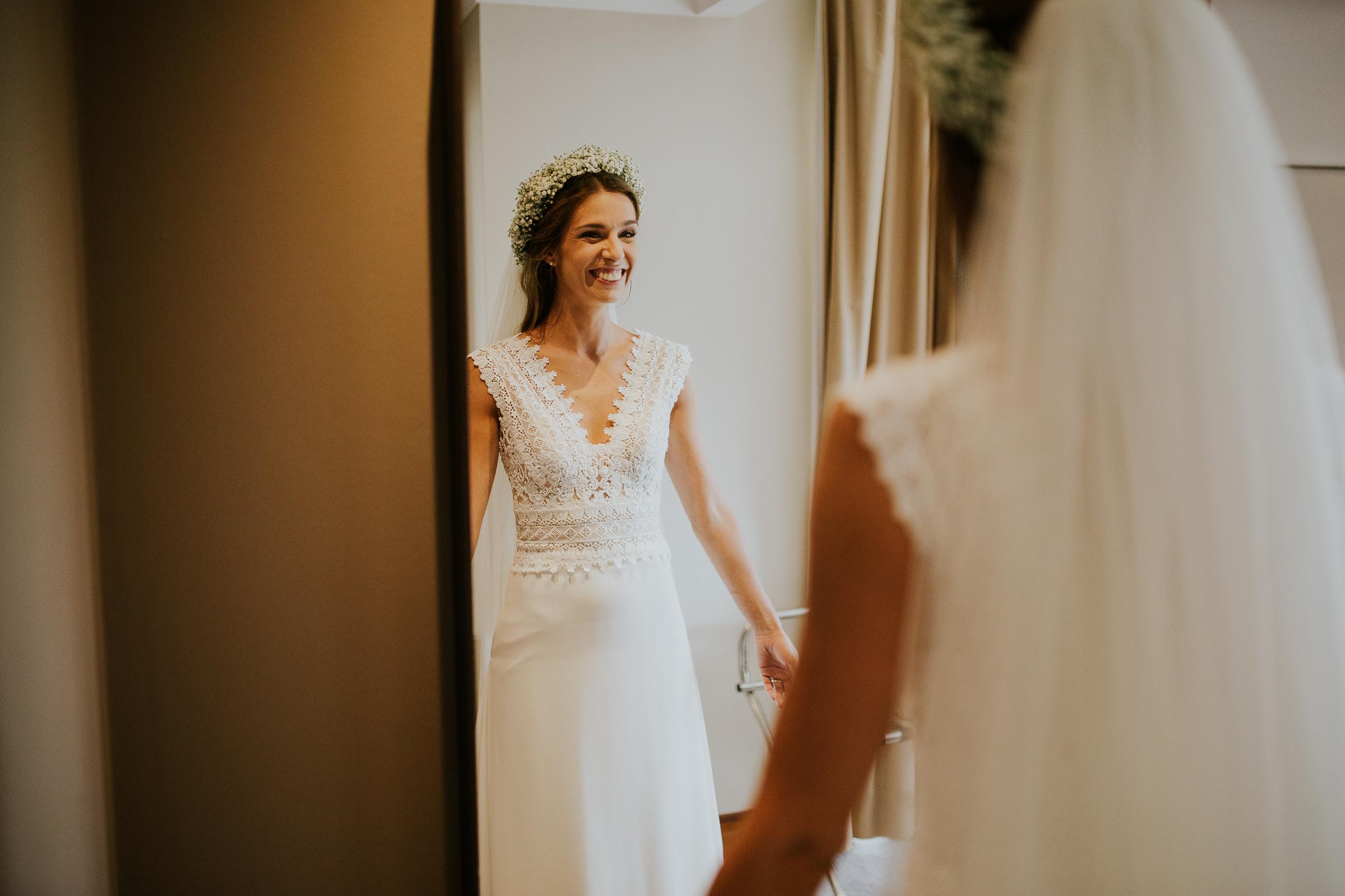 Reflection of happy bride looking trough the mirror