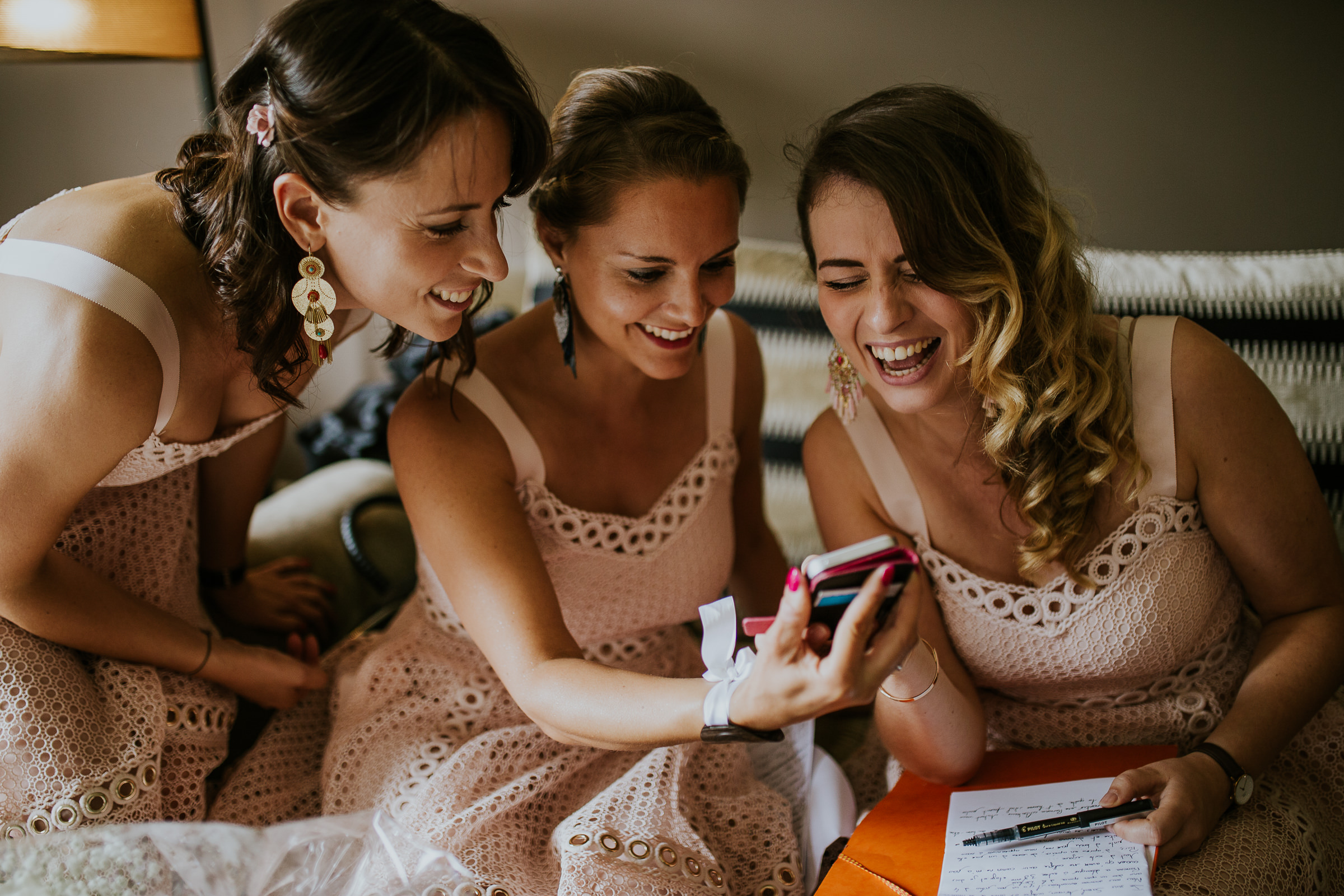Three happy bridesmaids laughing while watching their mobile phone.