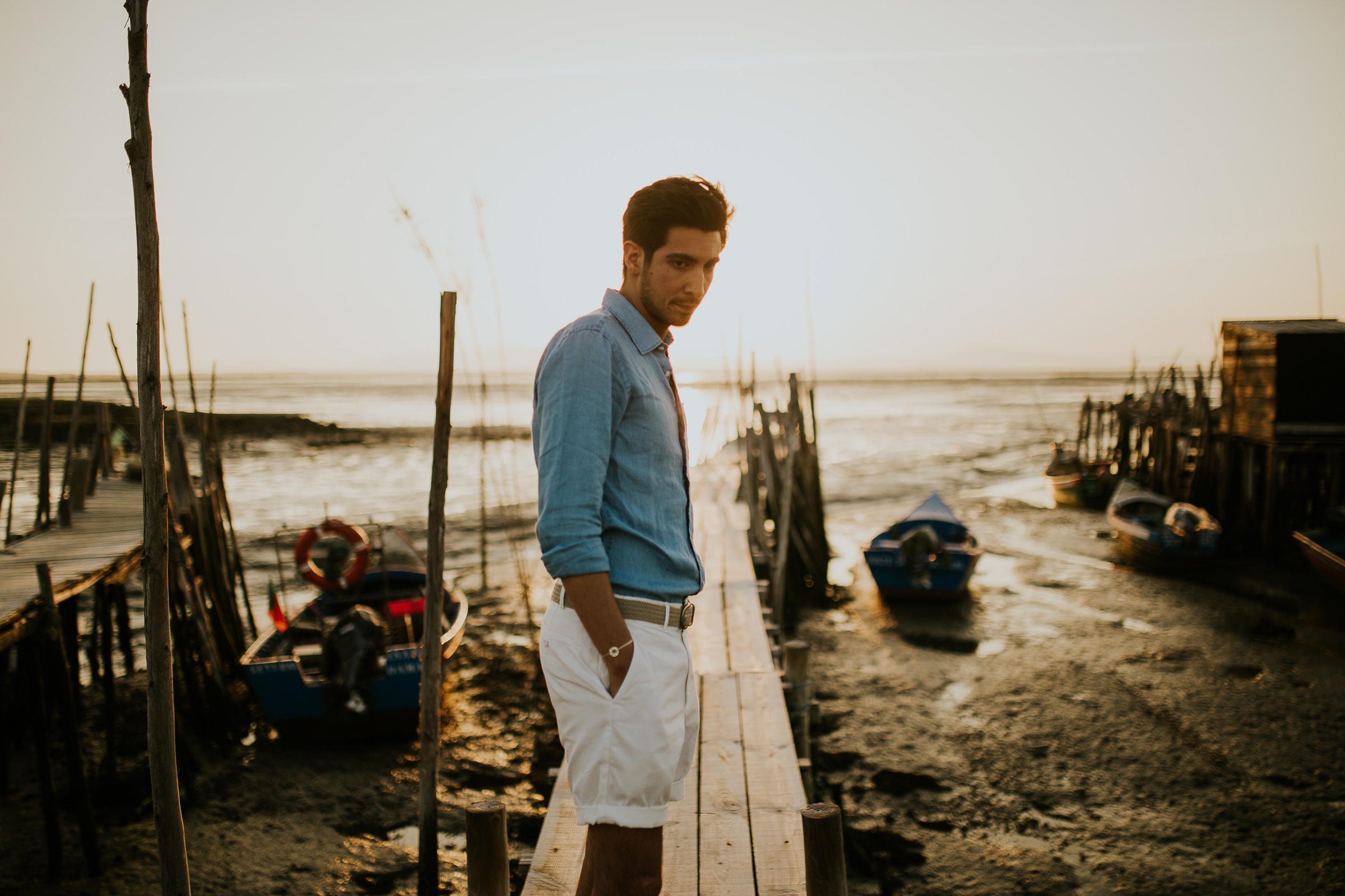 Centered guy looking down on a wooden dock during golden hour