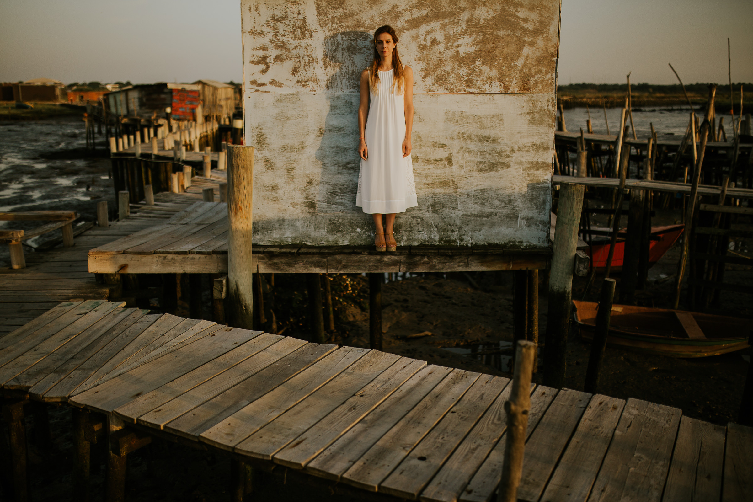 Centered Portrait of a woman dressing with a white dress on wooden dock during sunset