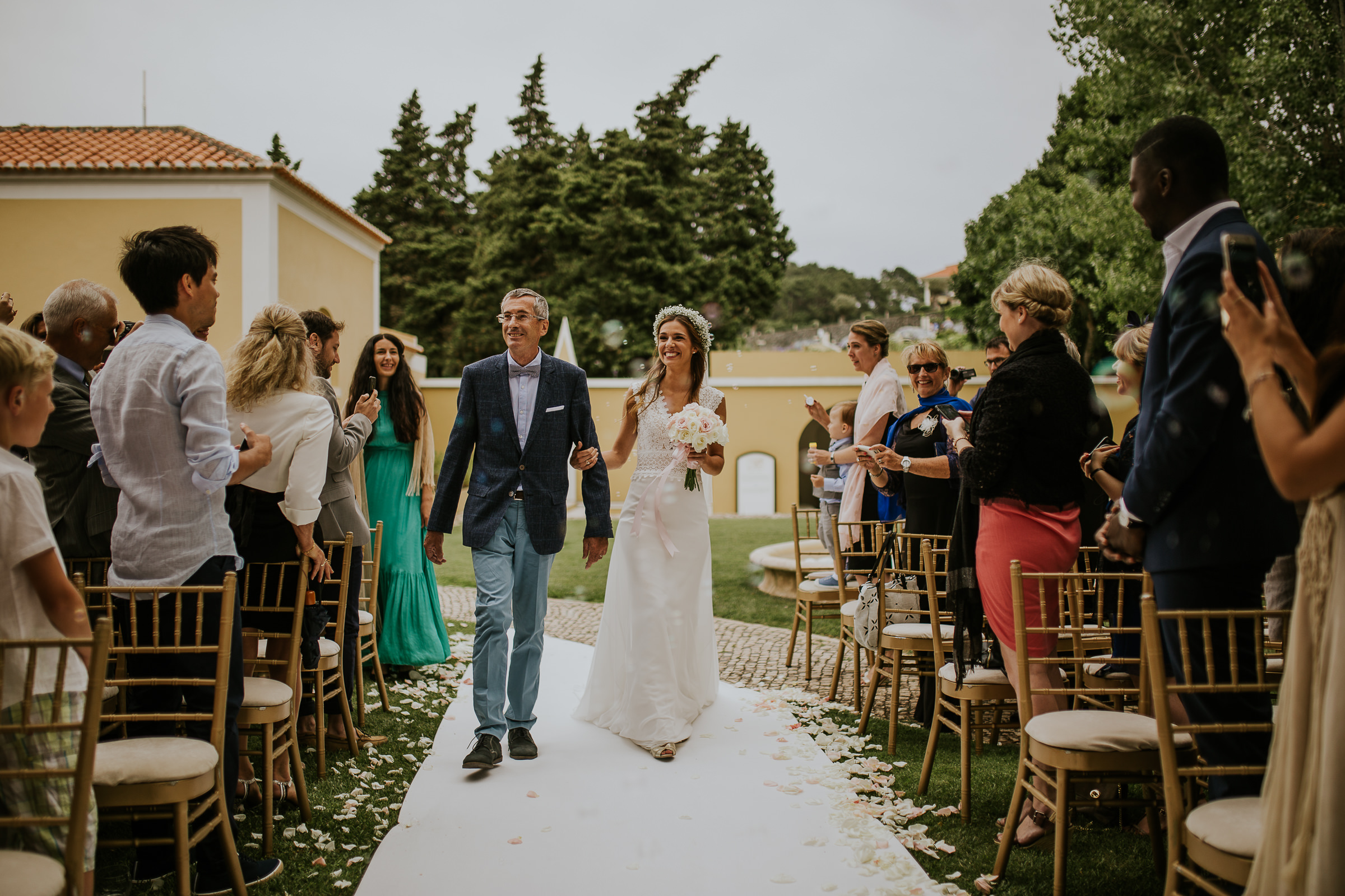 Father walk the bride down the aisle in an outdoor ceremony