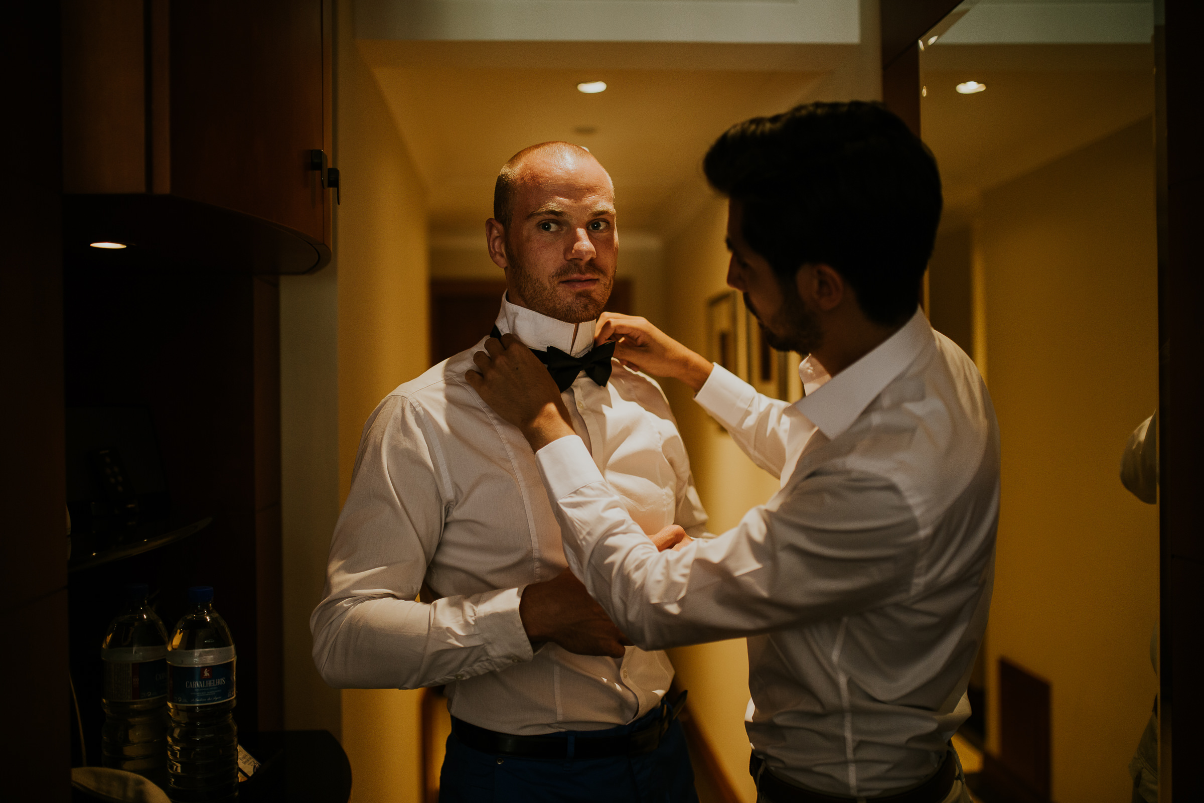 Groom helping the best man fixing his bow tie
