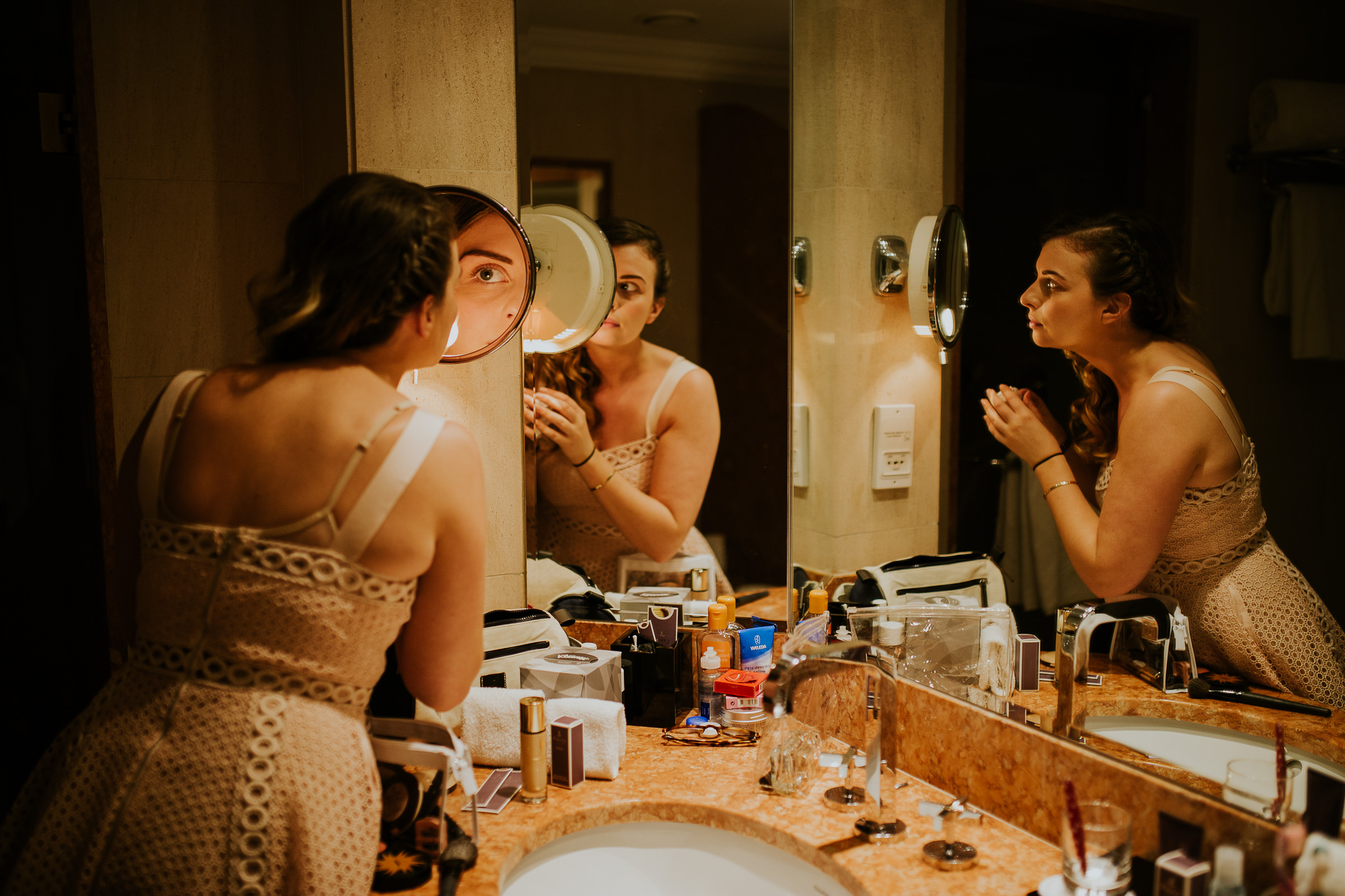 Multiple reflections on the mirrors of a Bridesmaid doing her make up