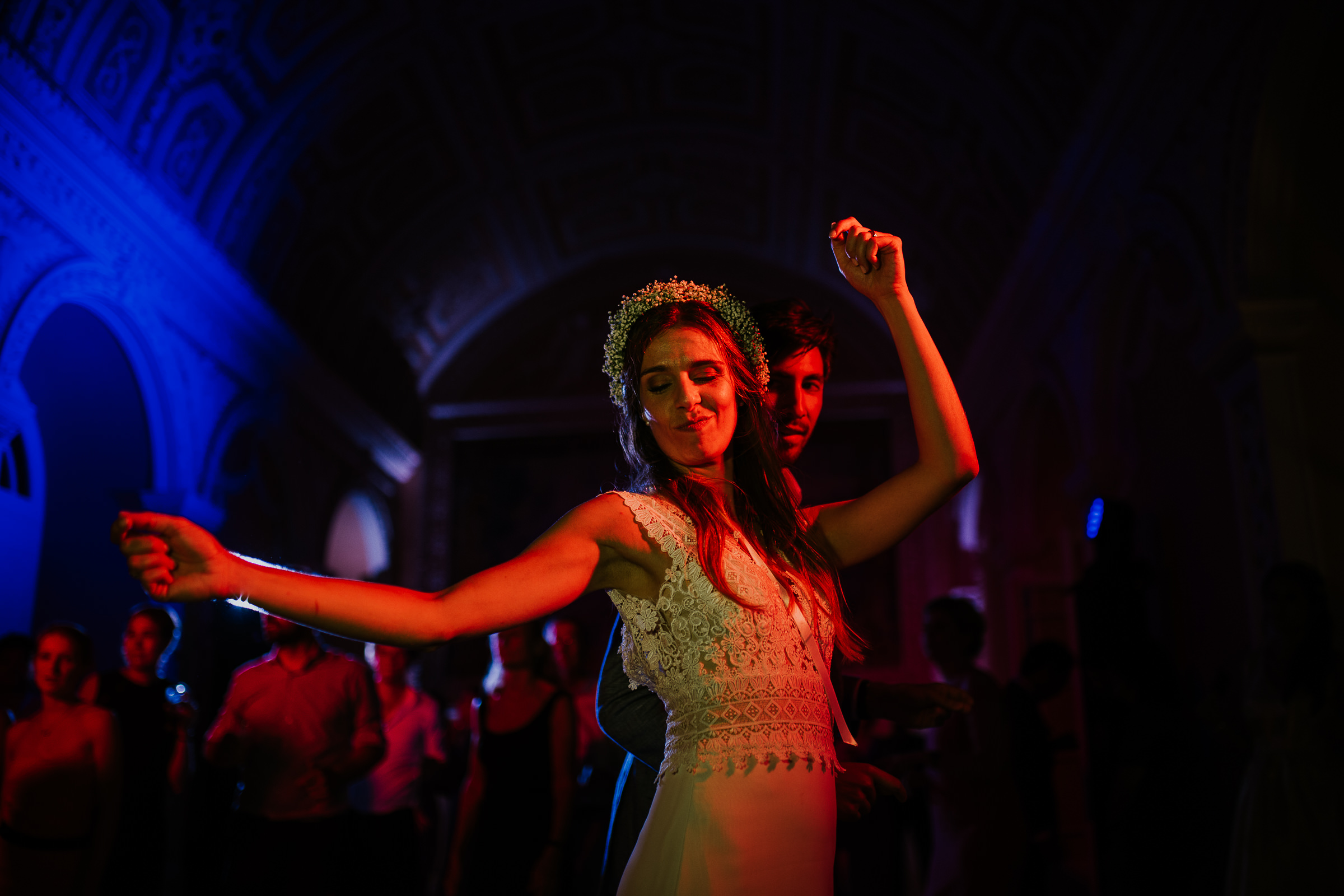 Bride dancing on wedding party with blue and red lights